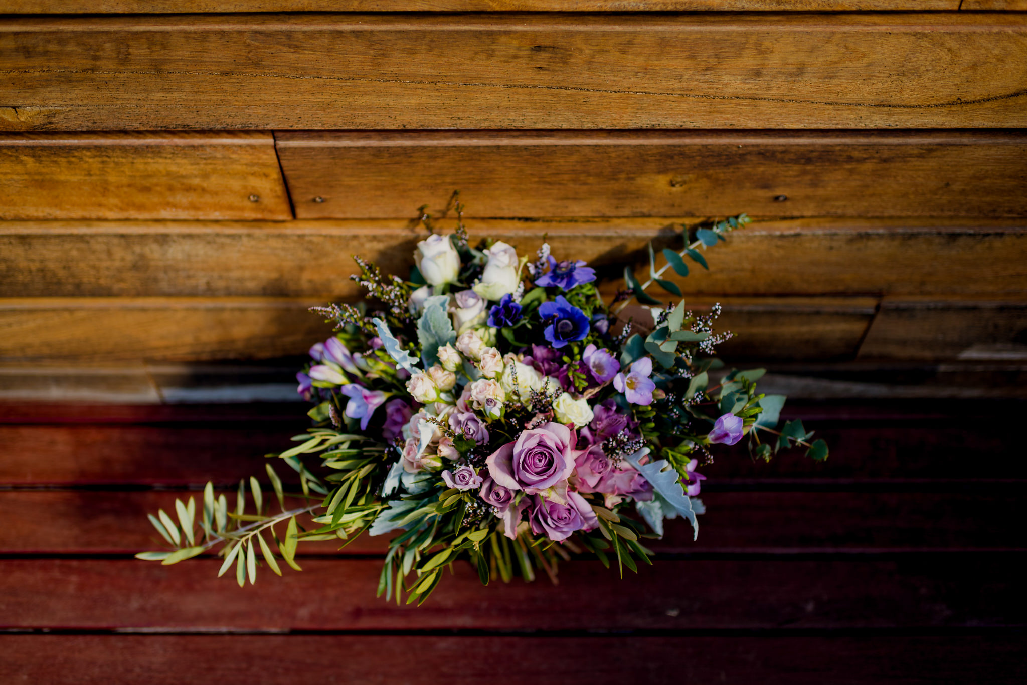 Purple flowers in a wedding bouquet placed on a wooden floor