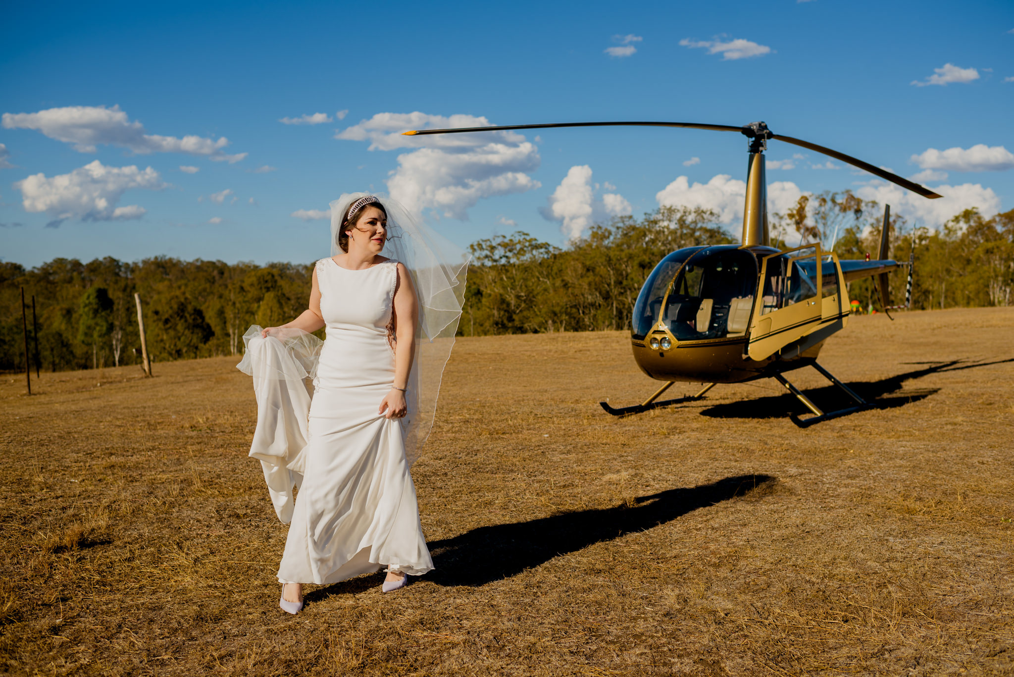 Bride holding her dress in front of a landed helicopter