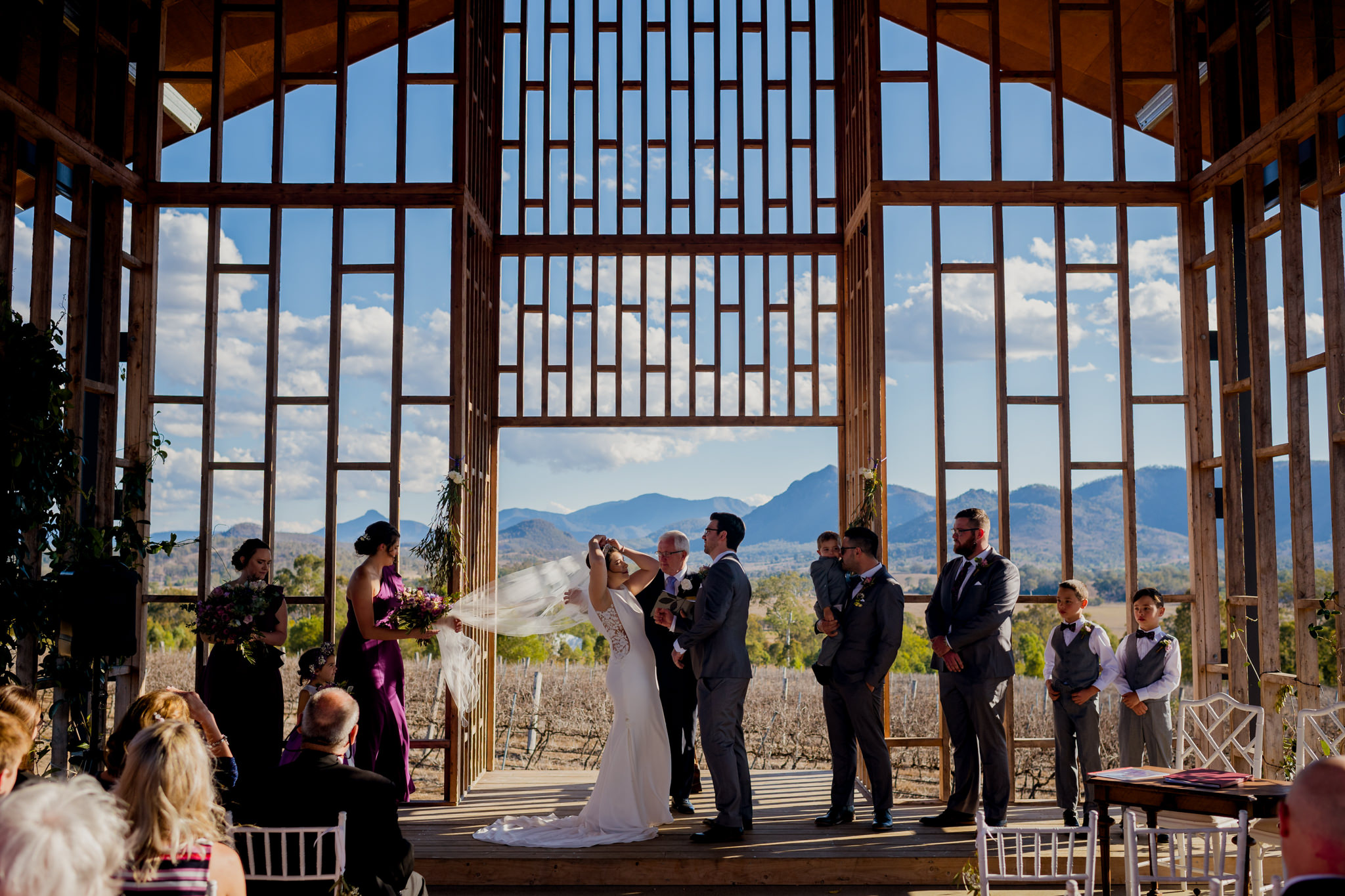 Bride and groom having their wedding ceremony in a wooden chapel at Kooroomba Lavender Farm