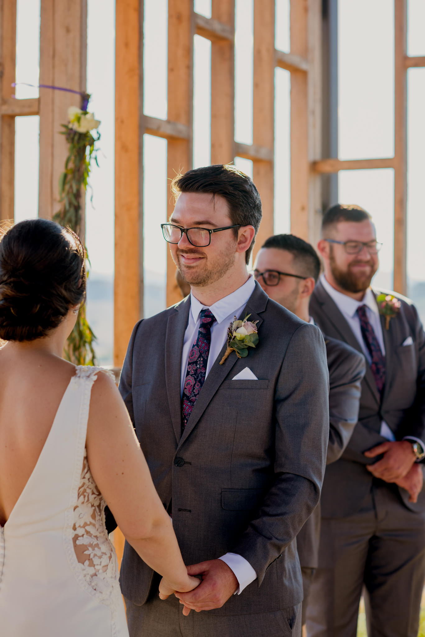 Groom in grey suit facing bride and smiling