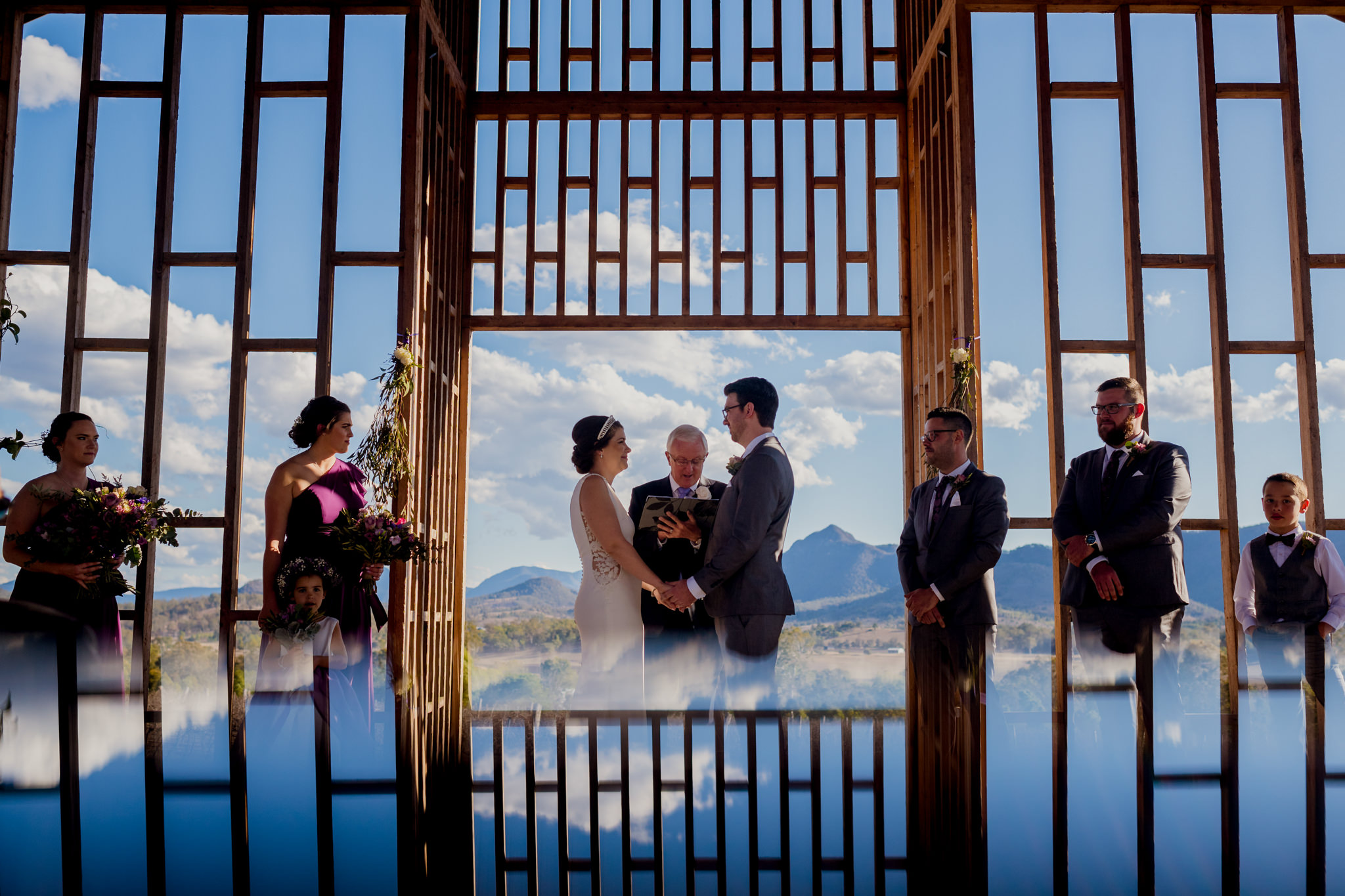 During a wedding ceremony at a wooden-framed chapel with the chapel detail reflected at the bottom of the photo
