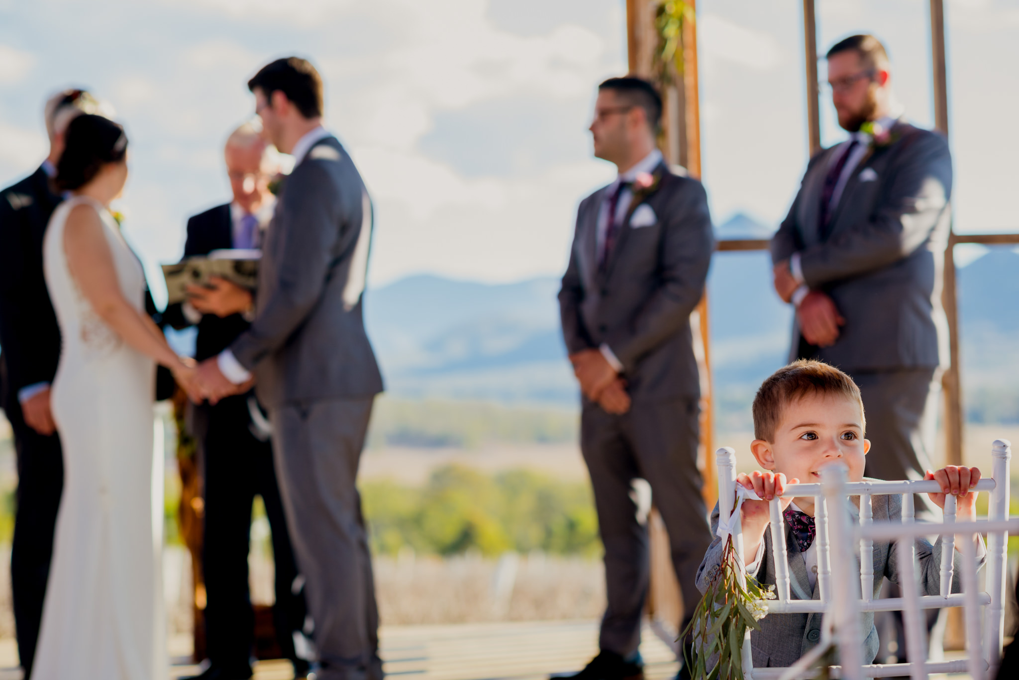 Young toddler in a suit looking over his chair during a wedding ceremony