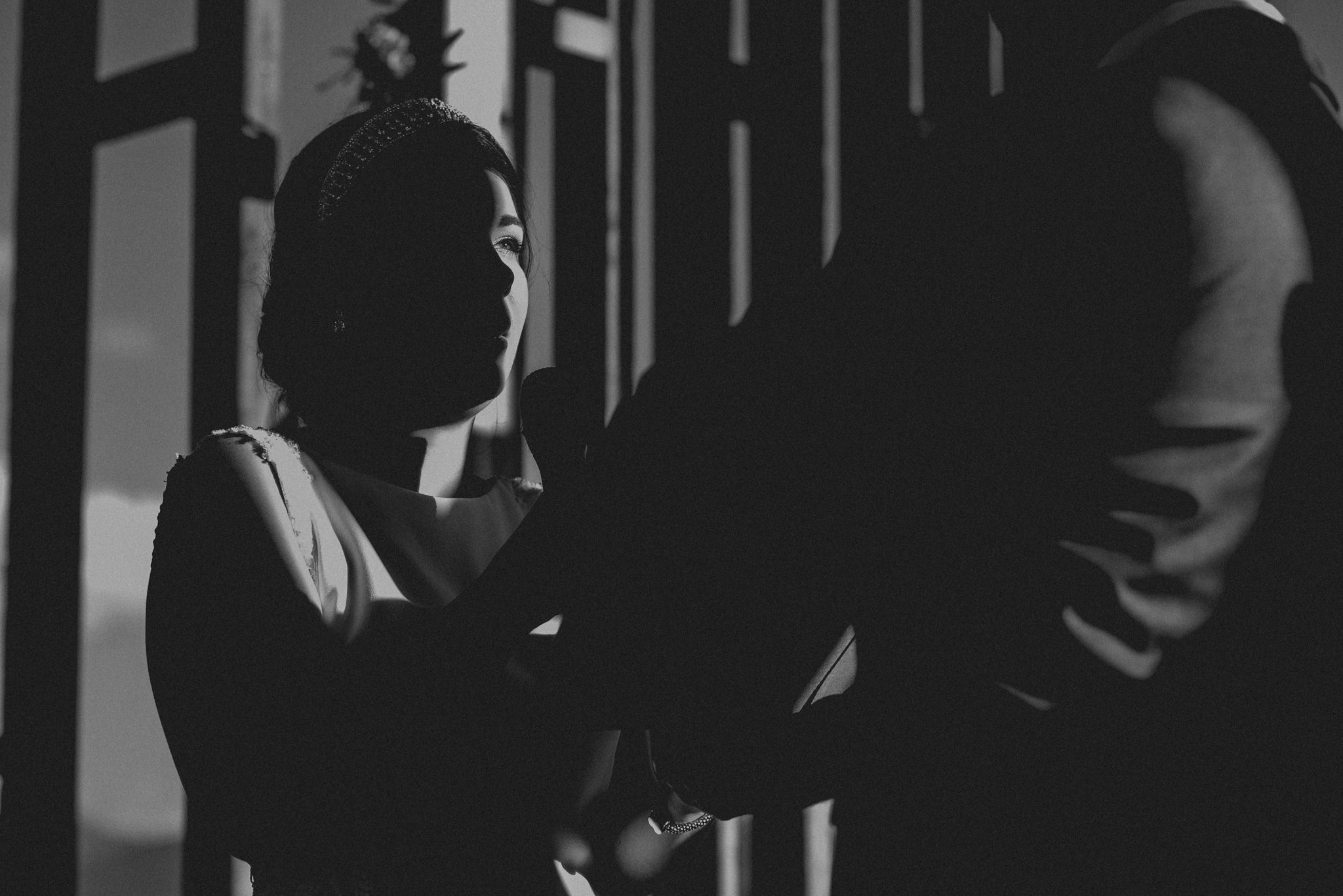 A bride making her vows with half her face enveloped in shadow and her eye in sunlight