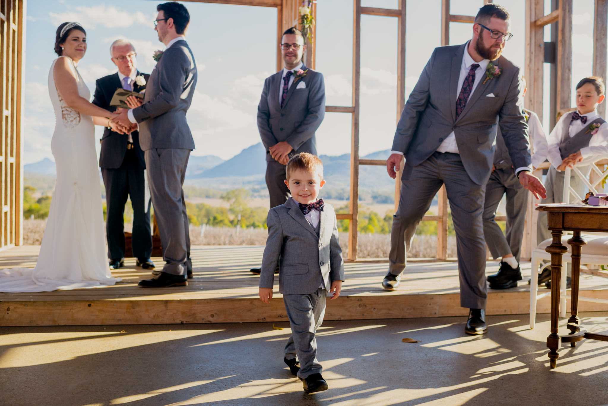 Young boy in suit walks around during a wedding ceremony
