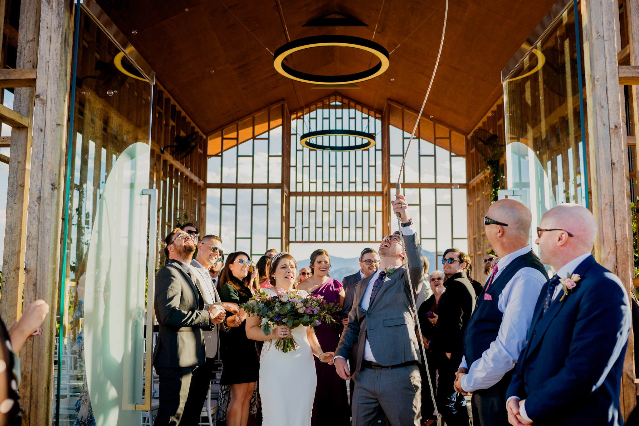 Groom swinging a bell rope at the end of the wedding cermeony