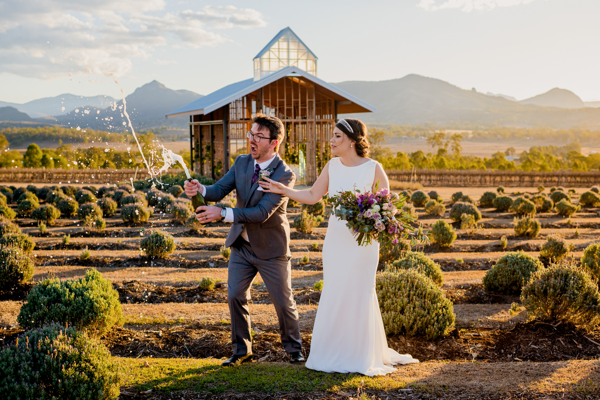 A bride and groom standing in a lavender farm as groom sprays champagne everywhere