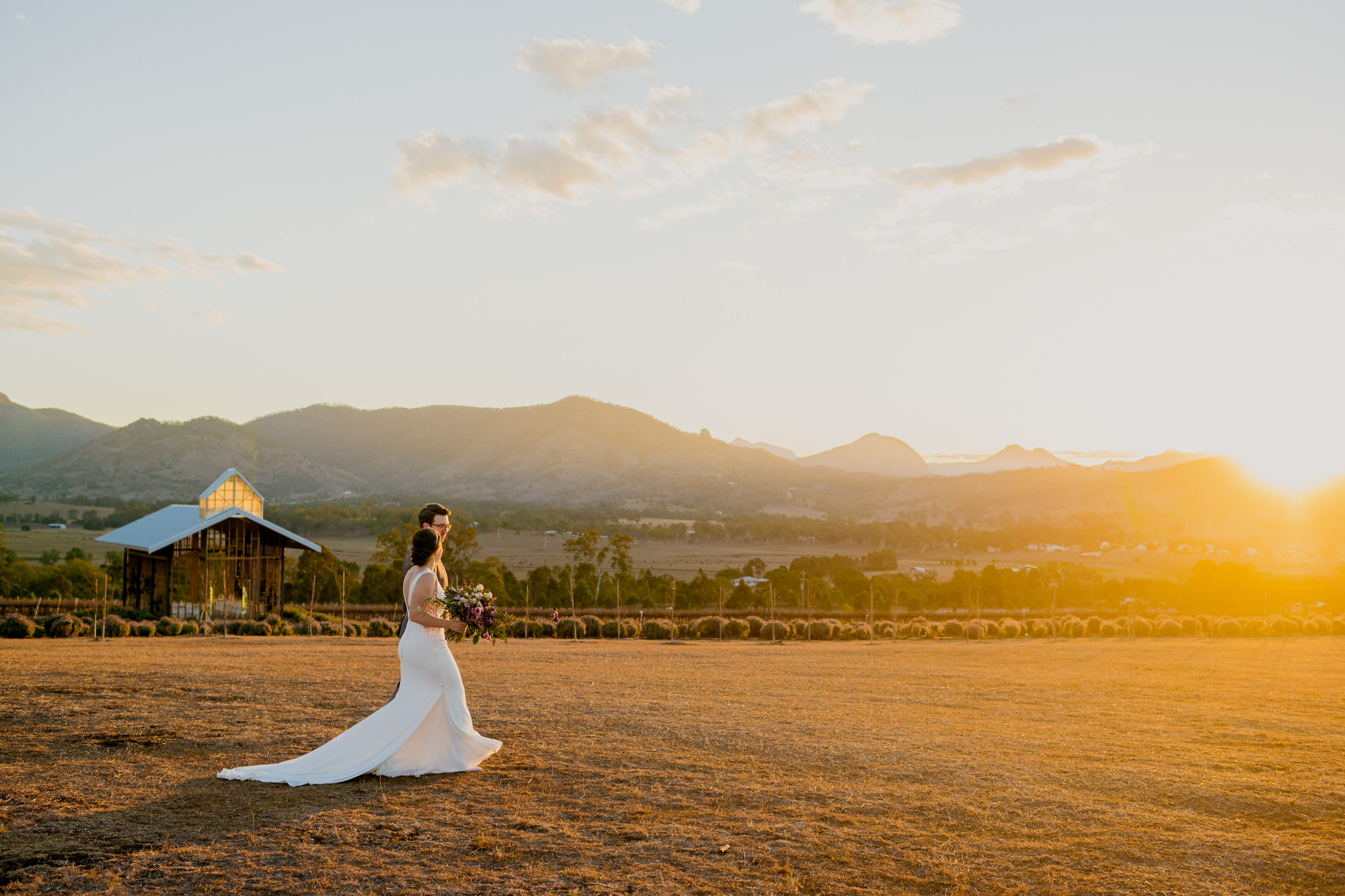 Bride and groom walking along grass with a lavender farm and mountains in the background
