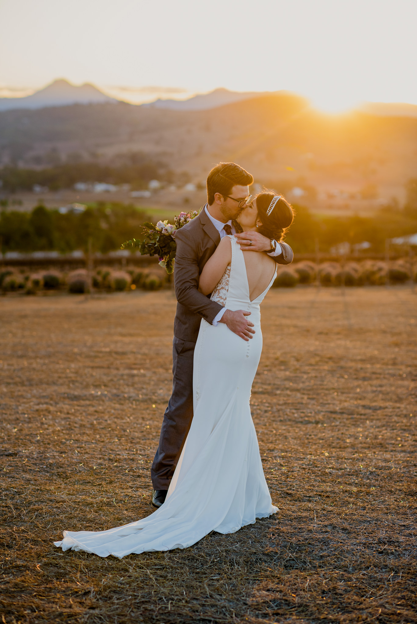 A bride and groom holding each other and kissing in front of a lavender farm