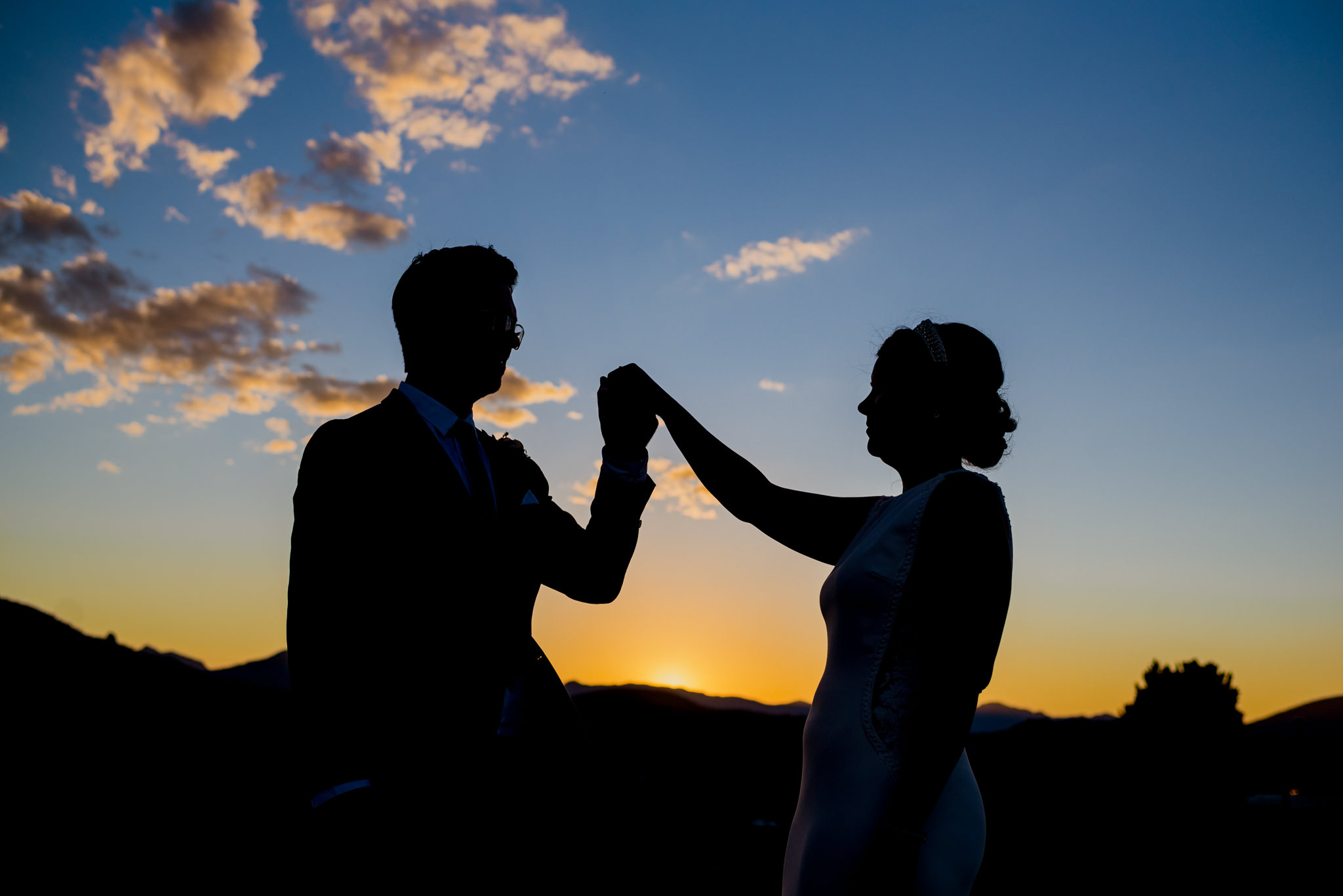 Silhouette of a man and woman holding hands in front of the afternoon sky
