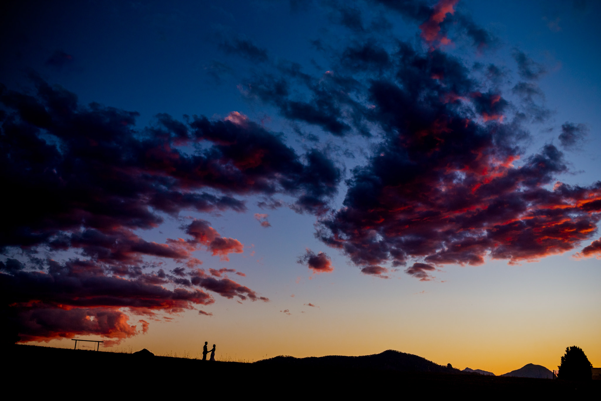 Red clouds float in a blue and orange sunset with a small silhouette of two people on a hill