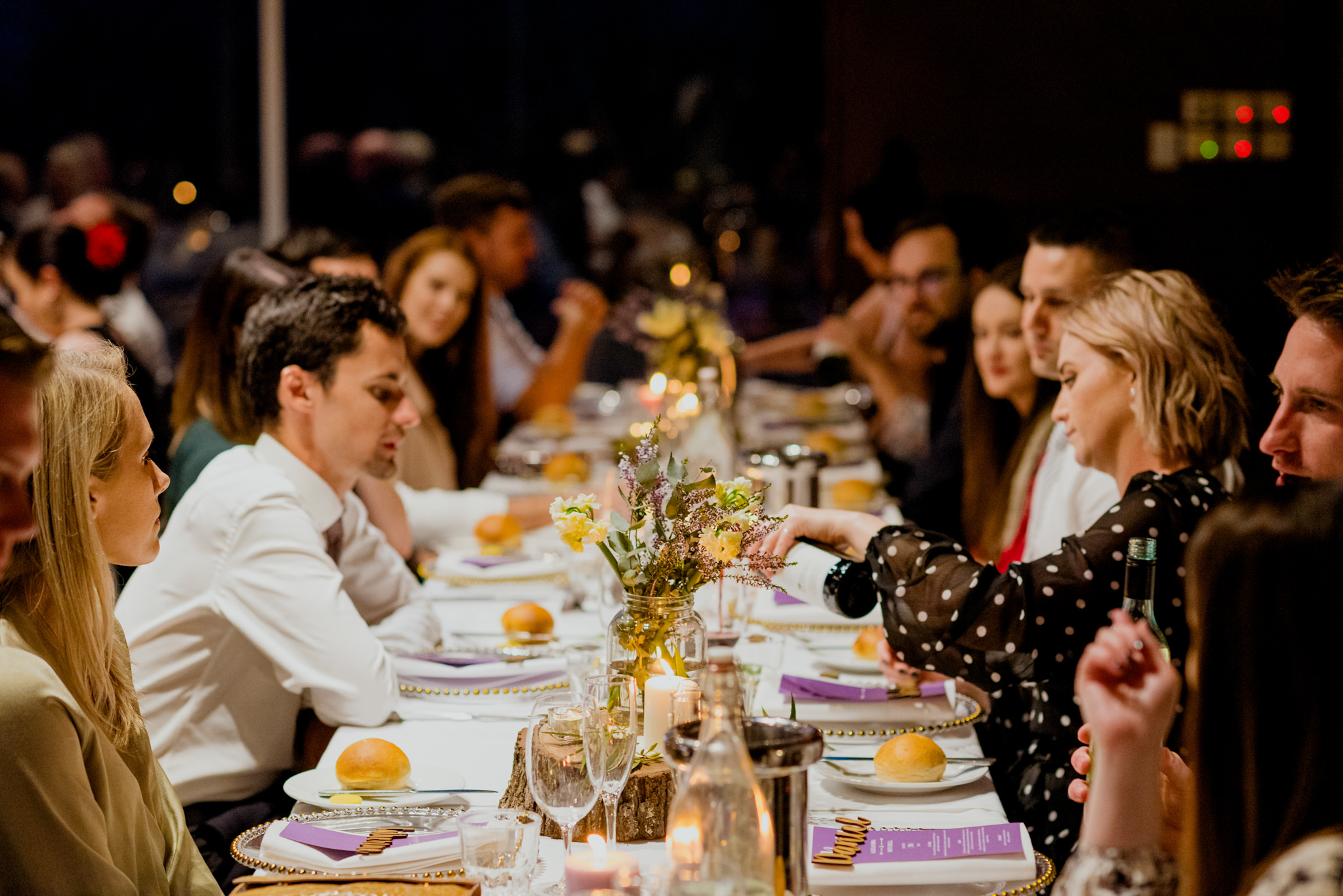 Dinner guests sit and mingle on long tables with flowers in the middle