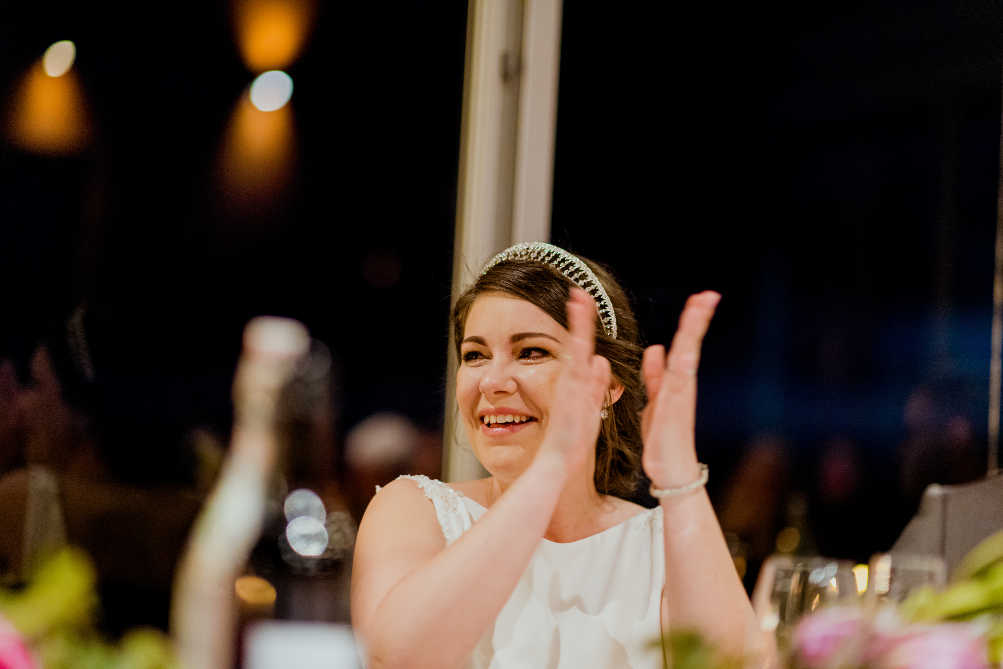 Bride laughing and clapping with tears in her eyes