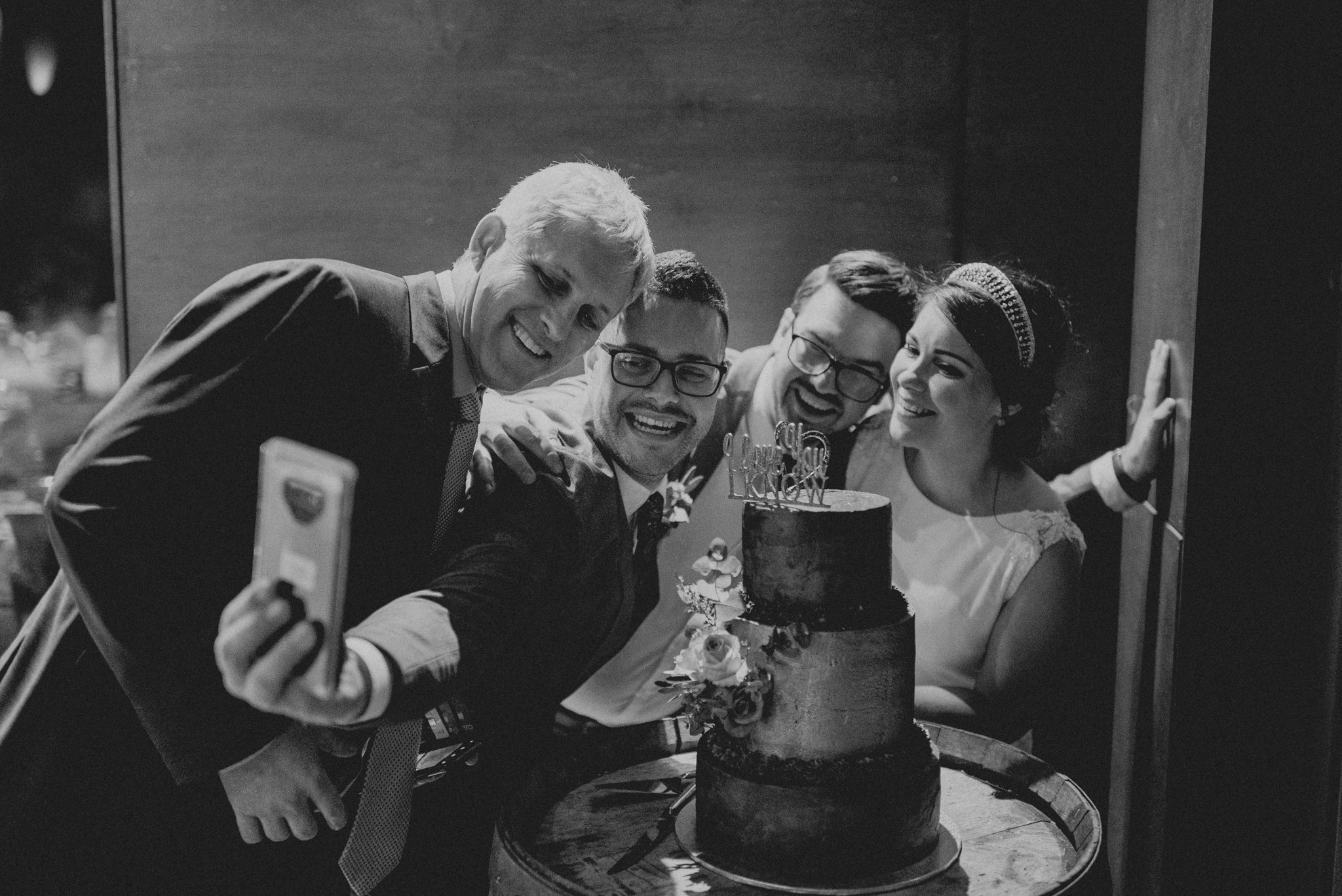 Four people laugh as they crowd together for a selfie in front of a wedding cake