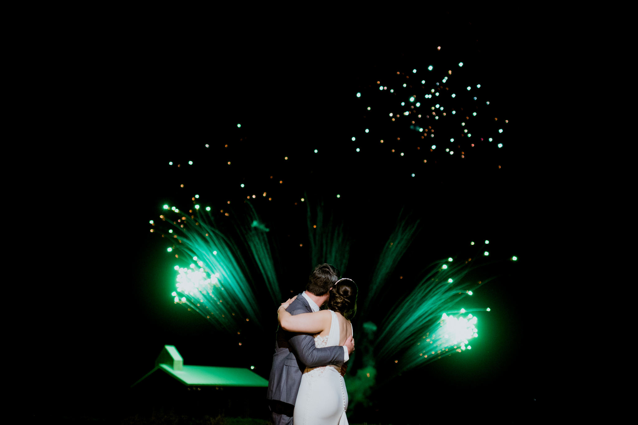 A groom and bride hug together as they watch green fireworks in the background