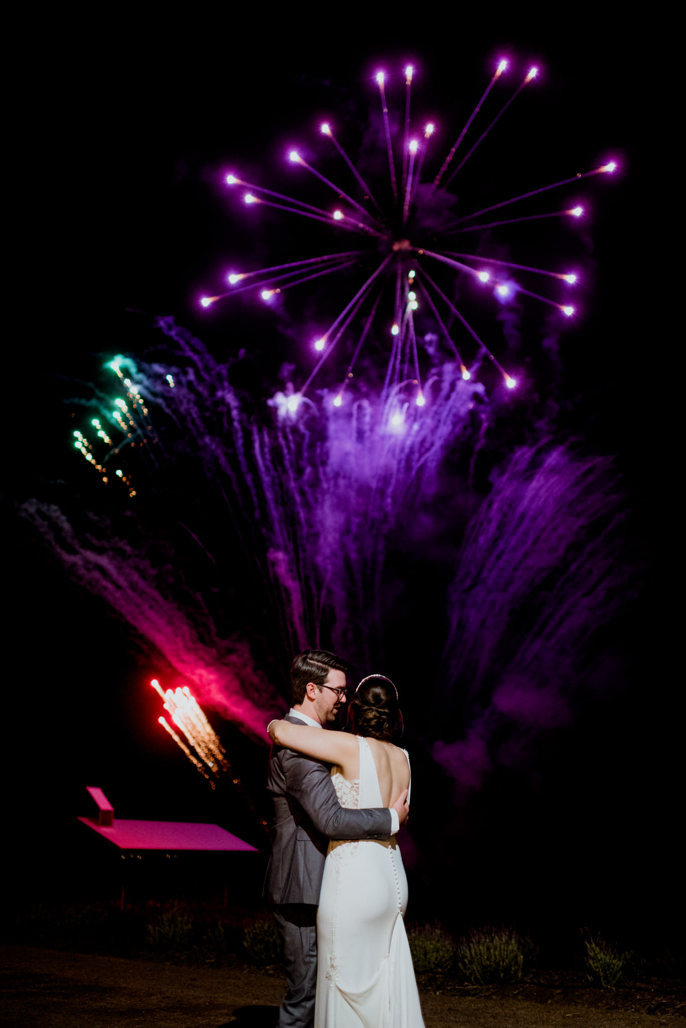 A bride watches a colourful fireworks display at Kooroomba as a groom holds and faces her