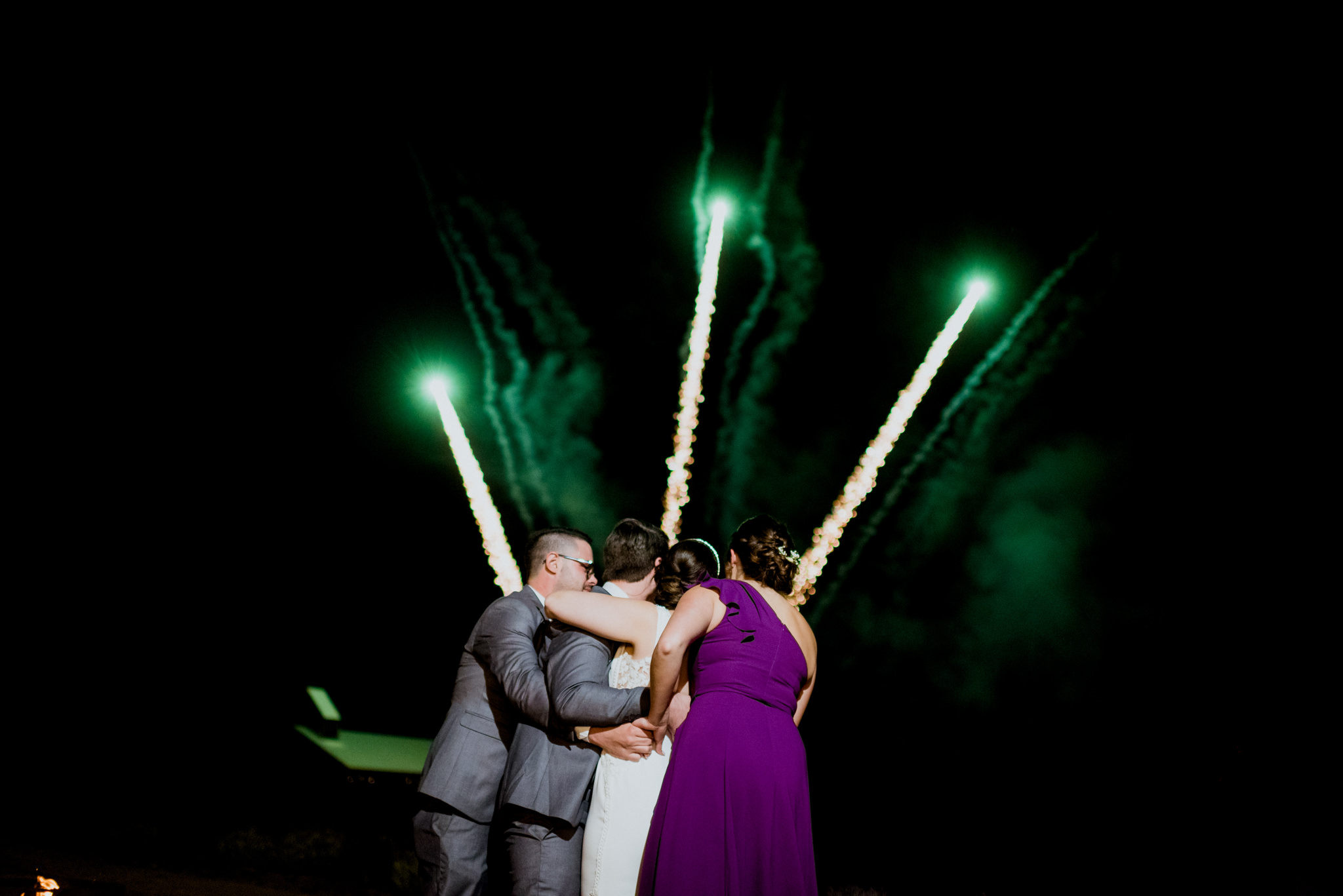 A wedding group hugs each other in front of a fireworks display