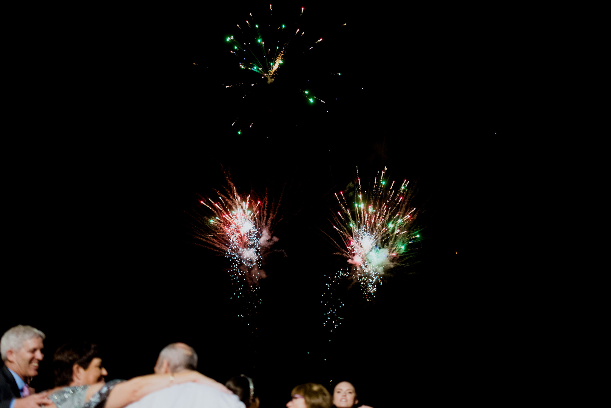 A small fireworks display with some people watching