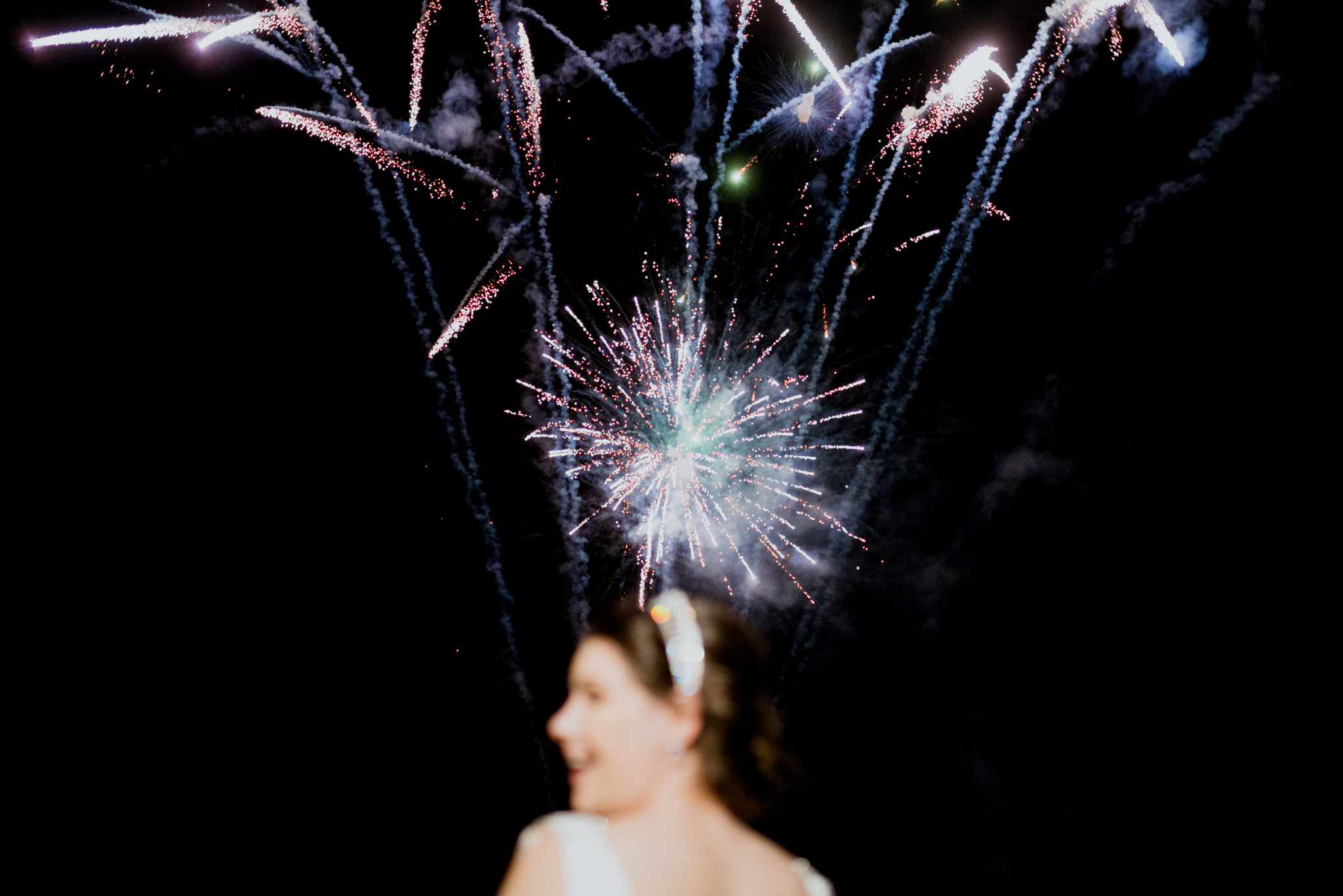 A small fireworks display at night with a bride looking on and laughing