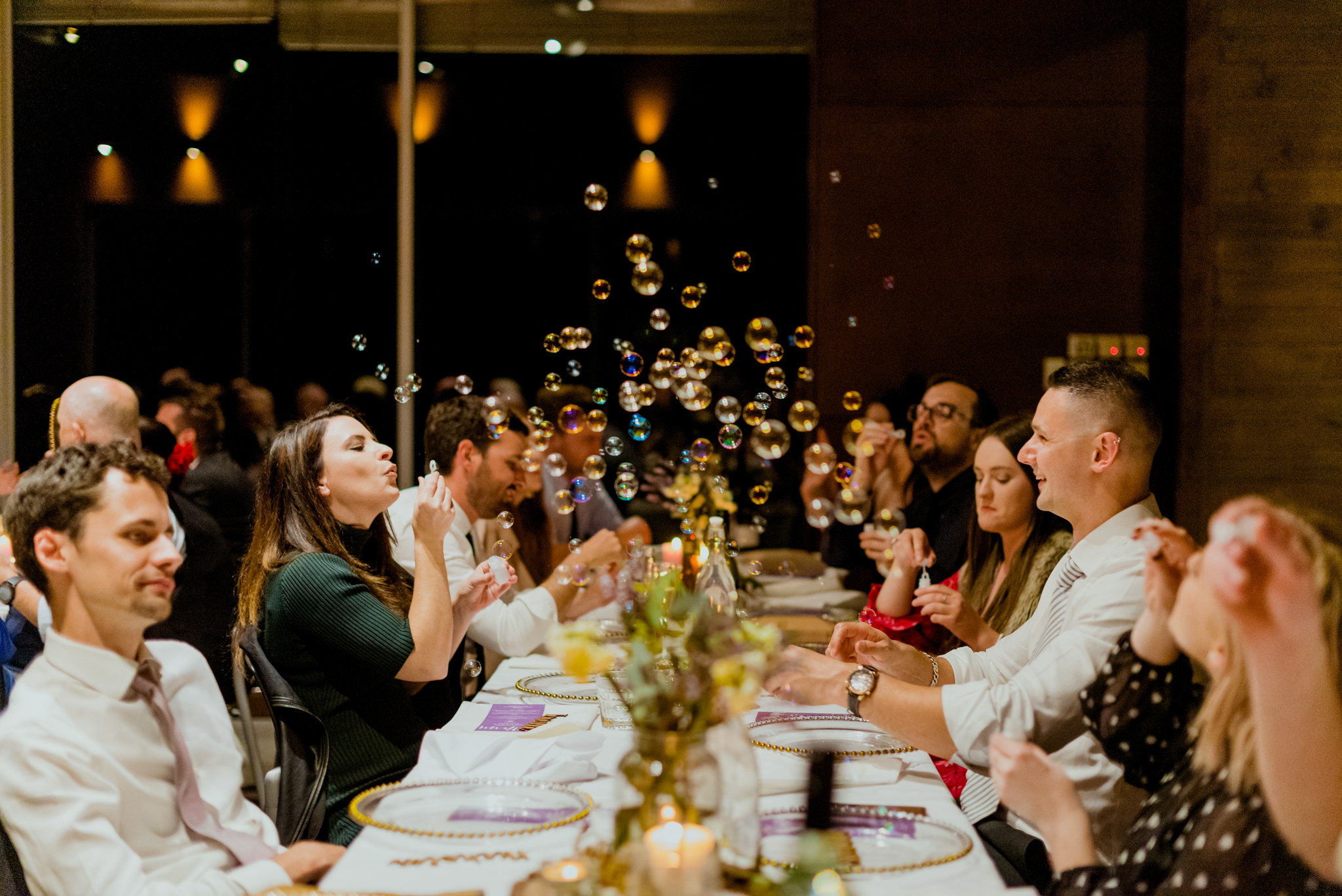 Guests blowing bubbles at a long dinner table