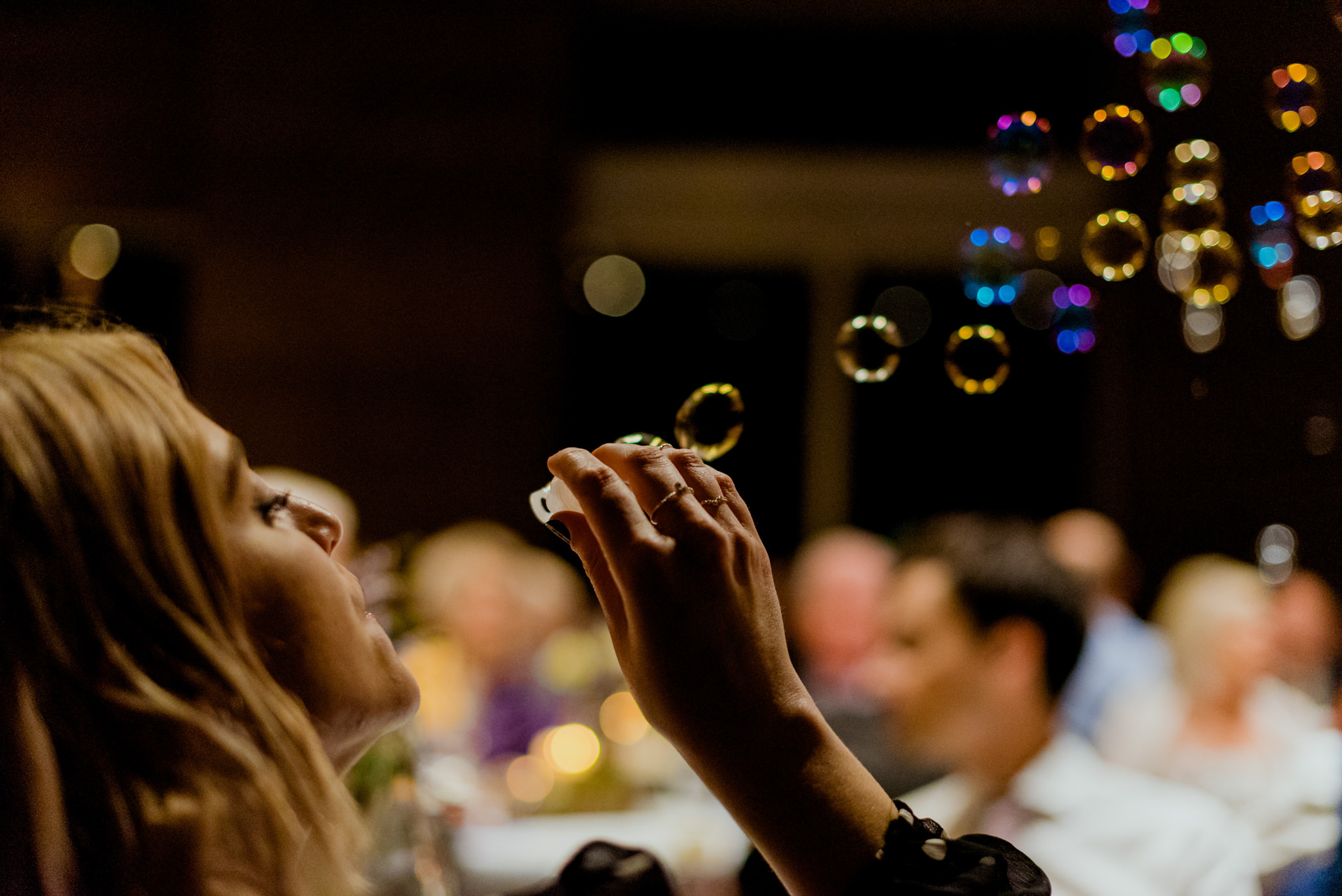 A blonde lady blows bubbles upwards at a dinner event