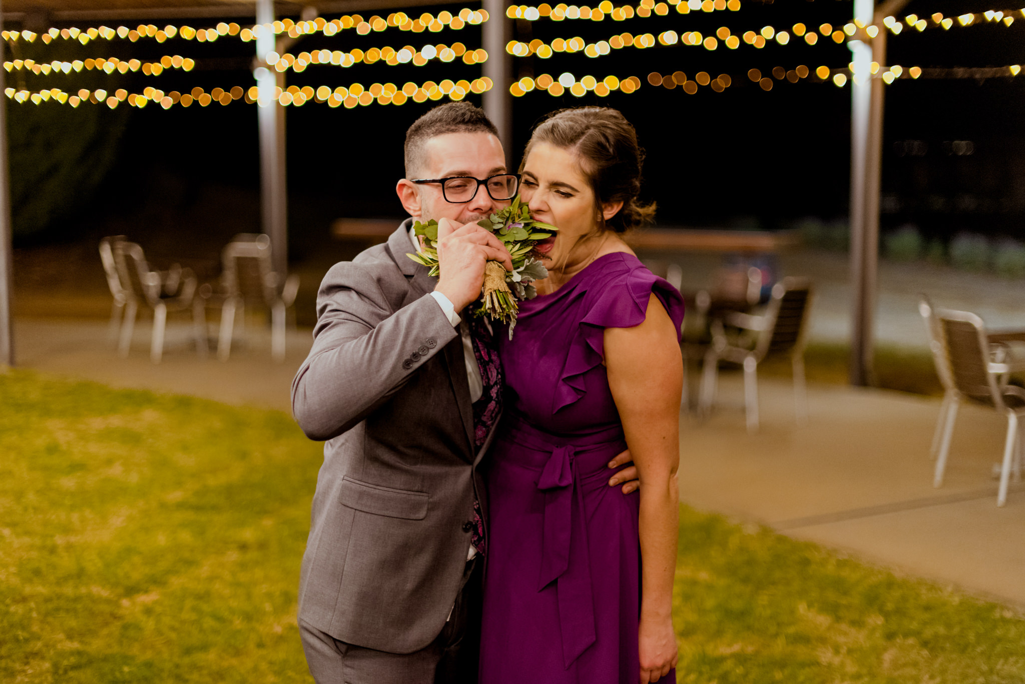 A man and a woman hug and pretend to eat a wedding bouquet