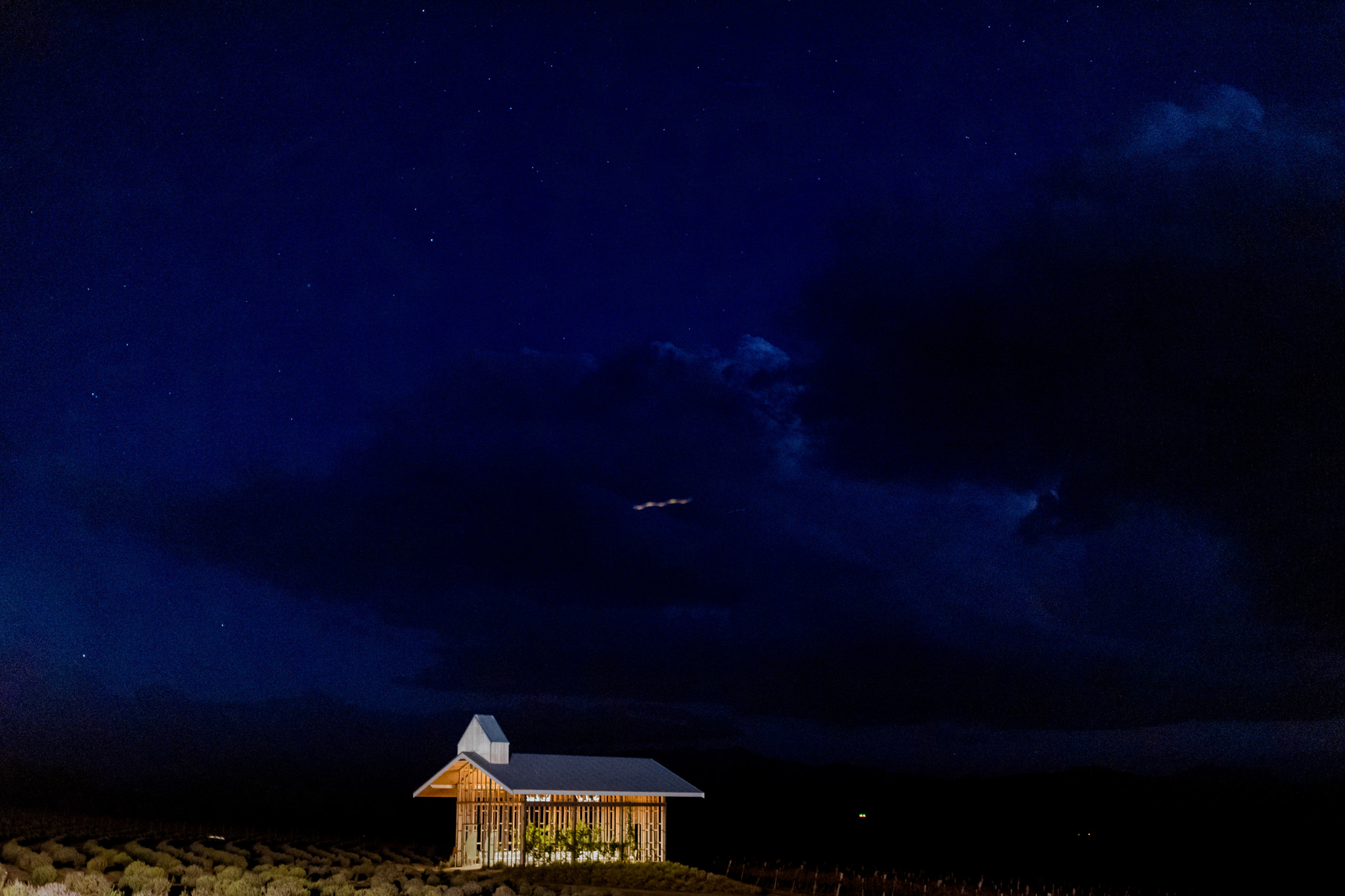 Kooroomba Chapel is lit up against the dark night sky and surrounding fields.