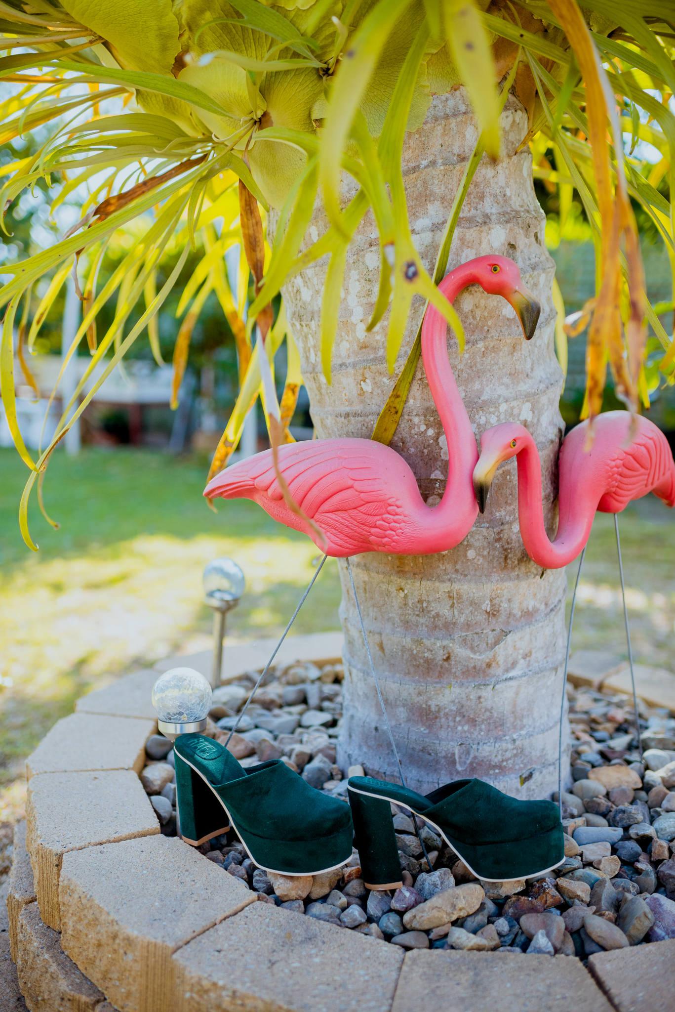 Green velvet high-heeled shoes underneath plastic flamingos under a palm tree