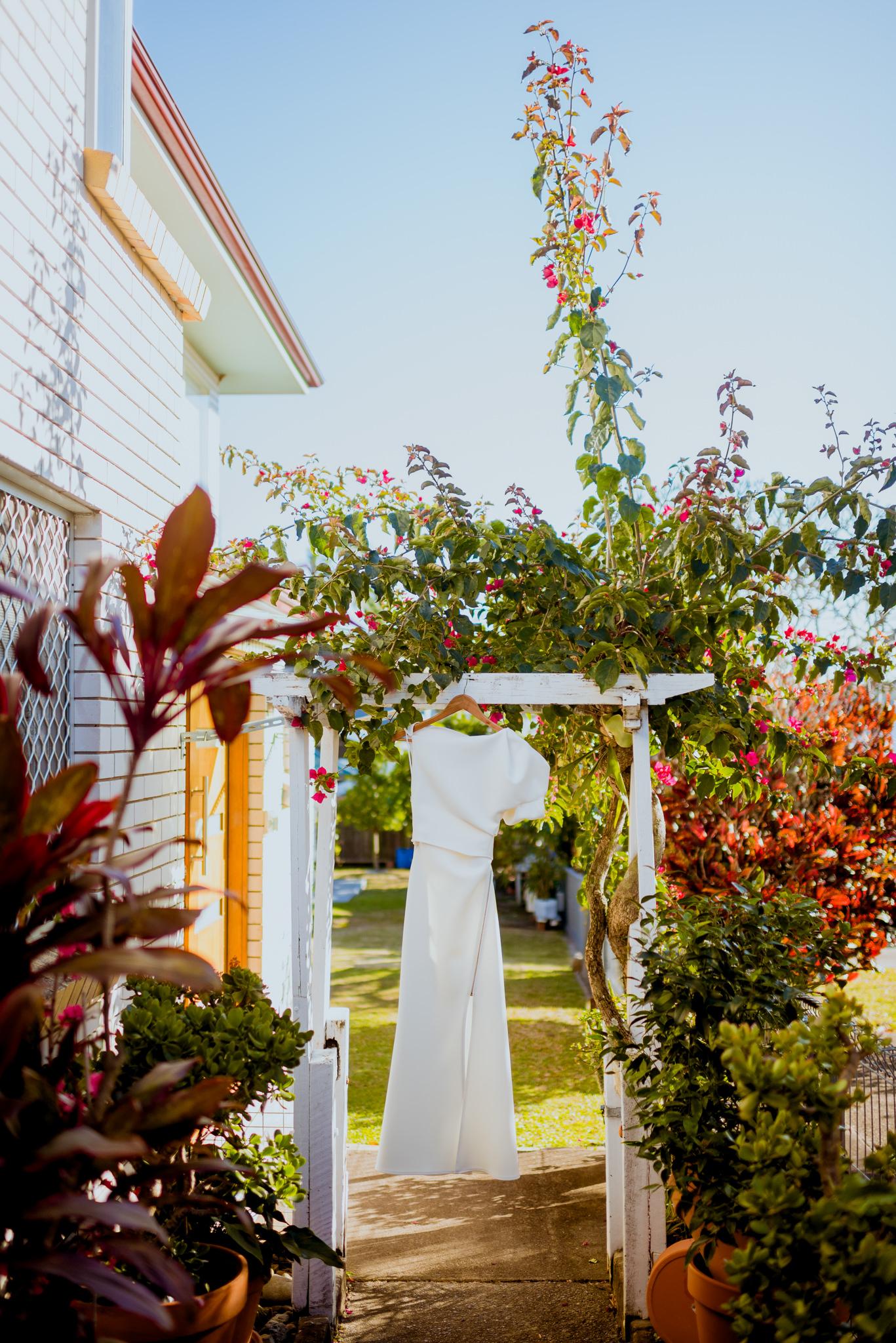 A modern white wedding dress hanging from a garden arbour in a backyard