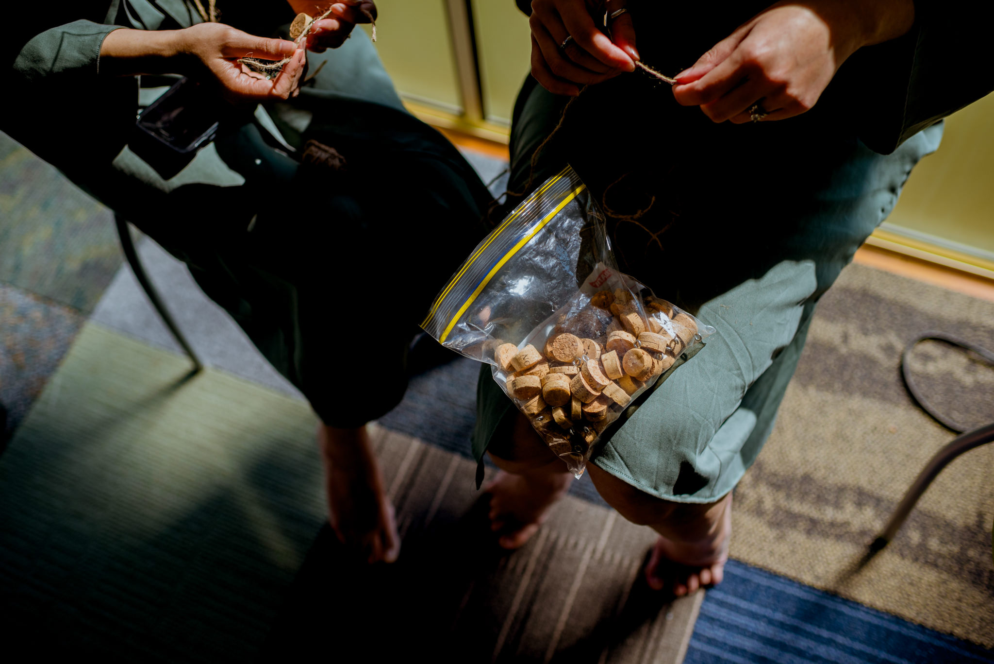 Two women tying string on corks with a bag of corks on one of their laps