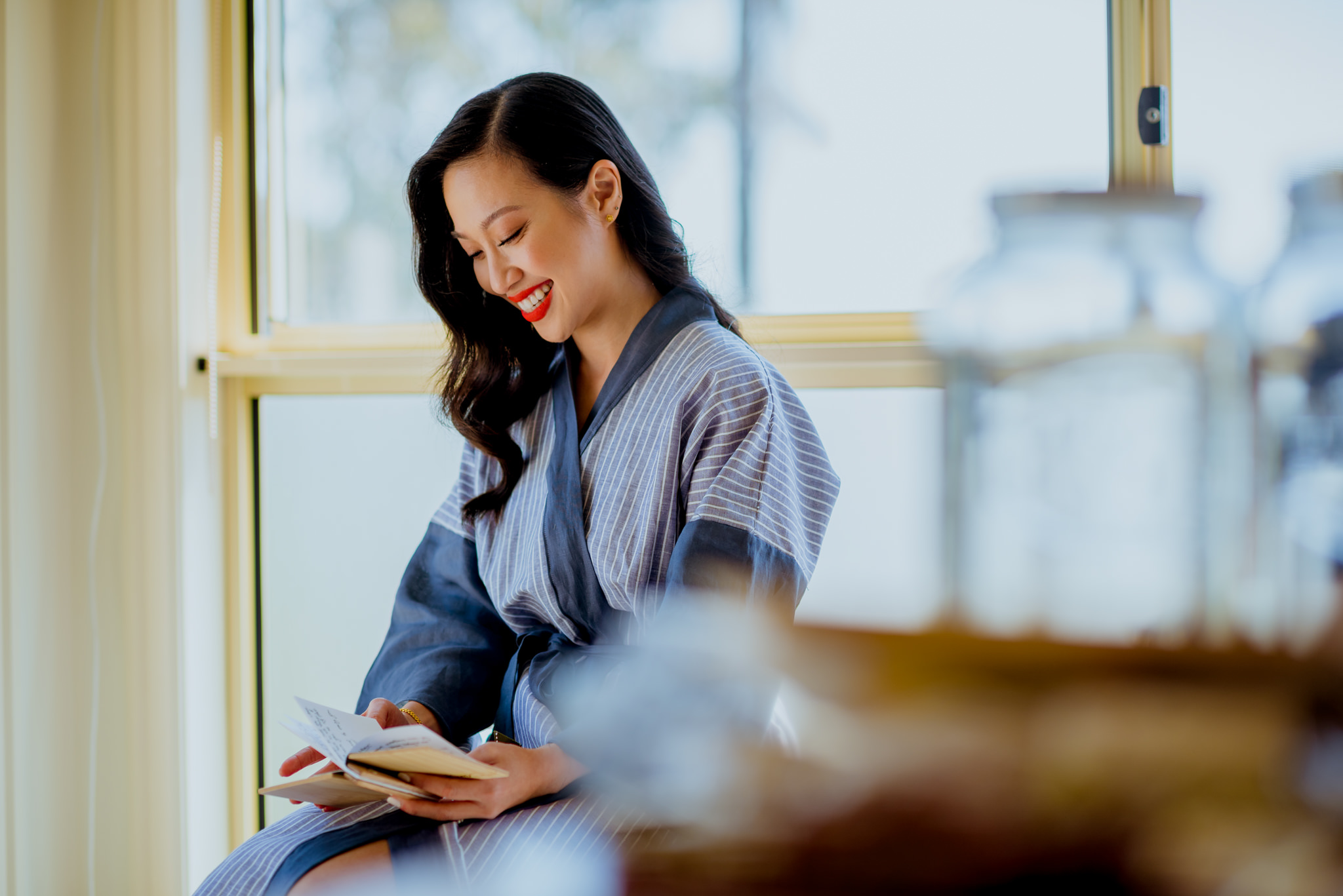 Asian woman smiles as she reads a personalised wooden booklet