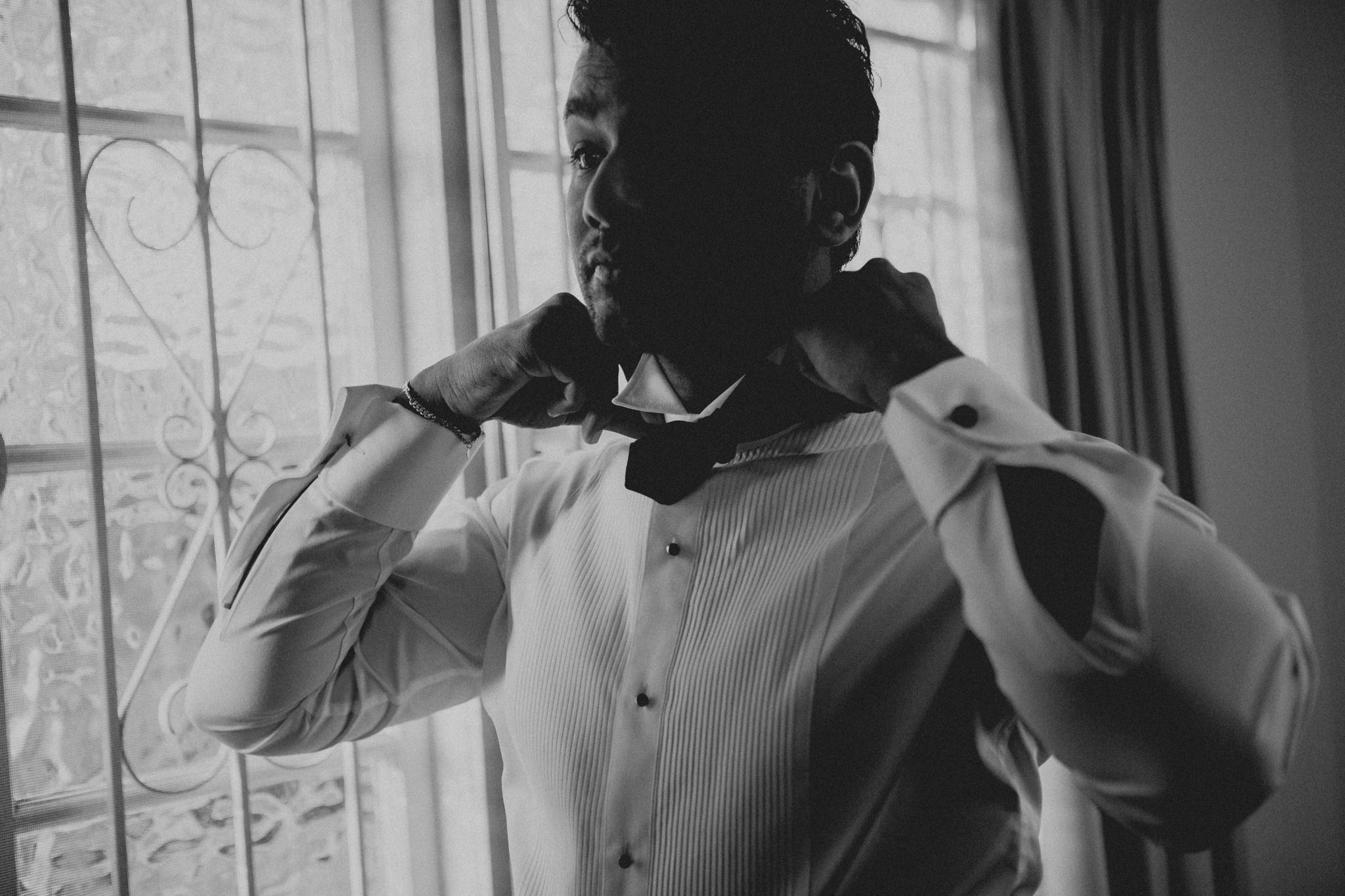 A man stands next to a window as he puts on a bow-tie