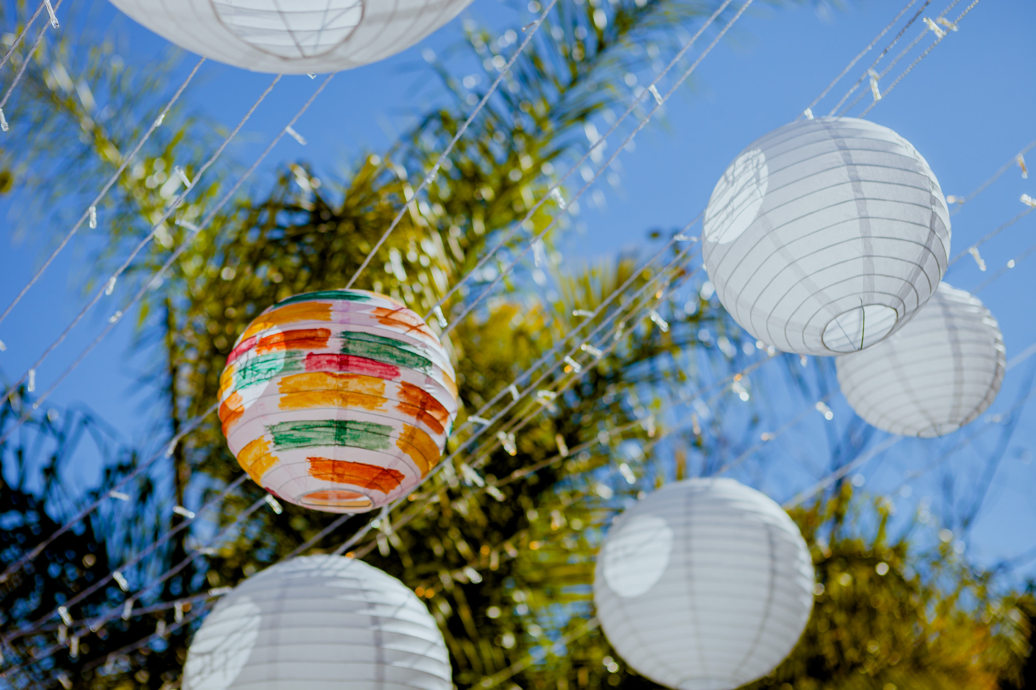 White lanterns strung up on lines of fairy lights, with one lantern painted colourfully