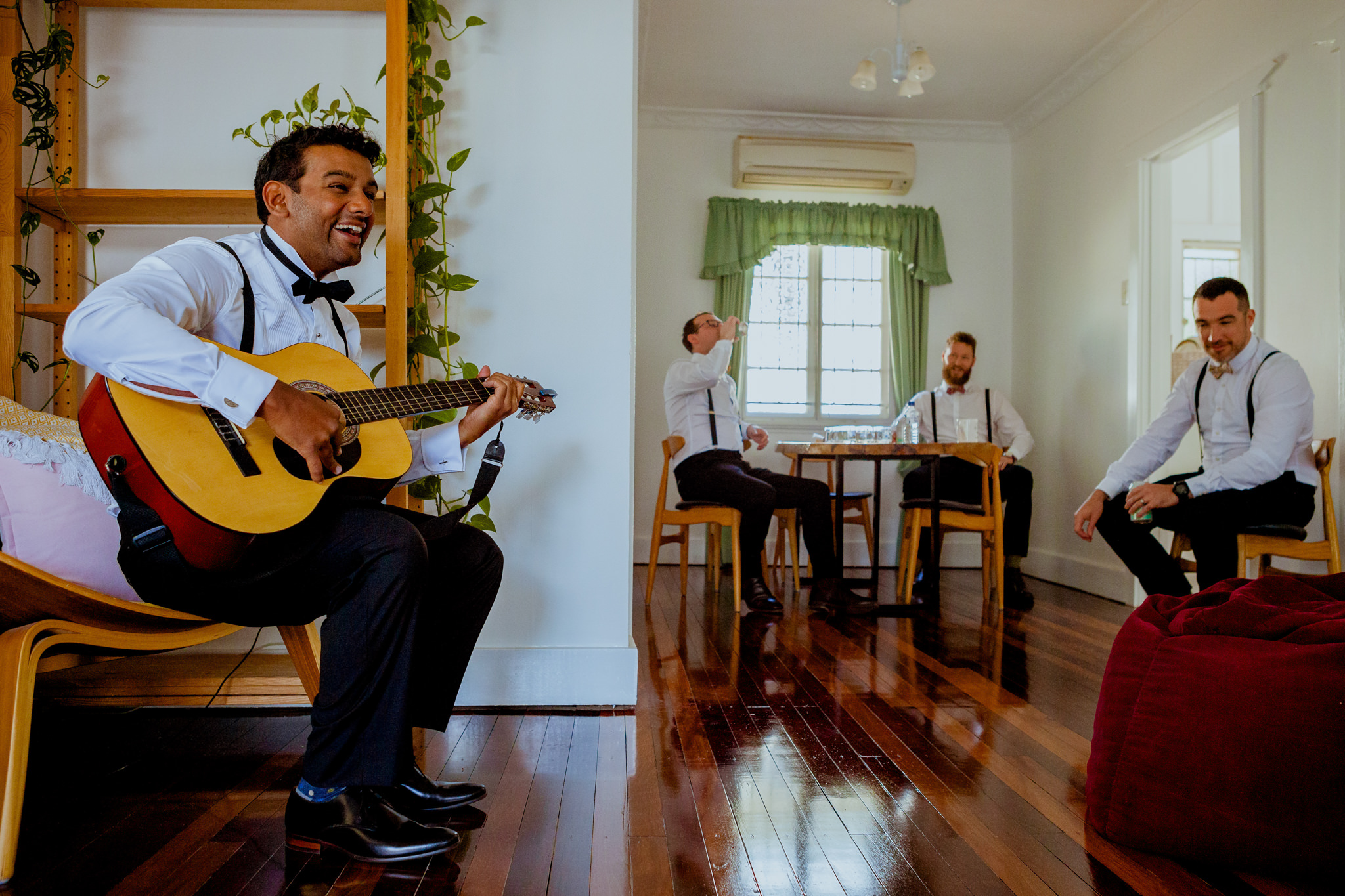 Men in suits laugh as they sit together in a room while one plays guitar