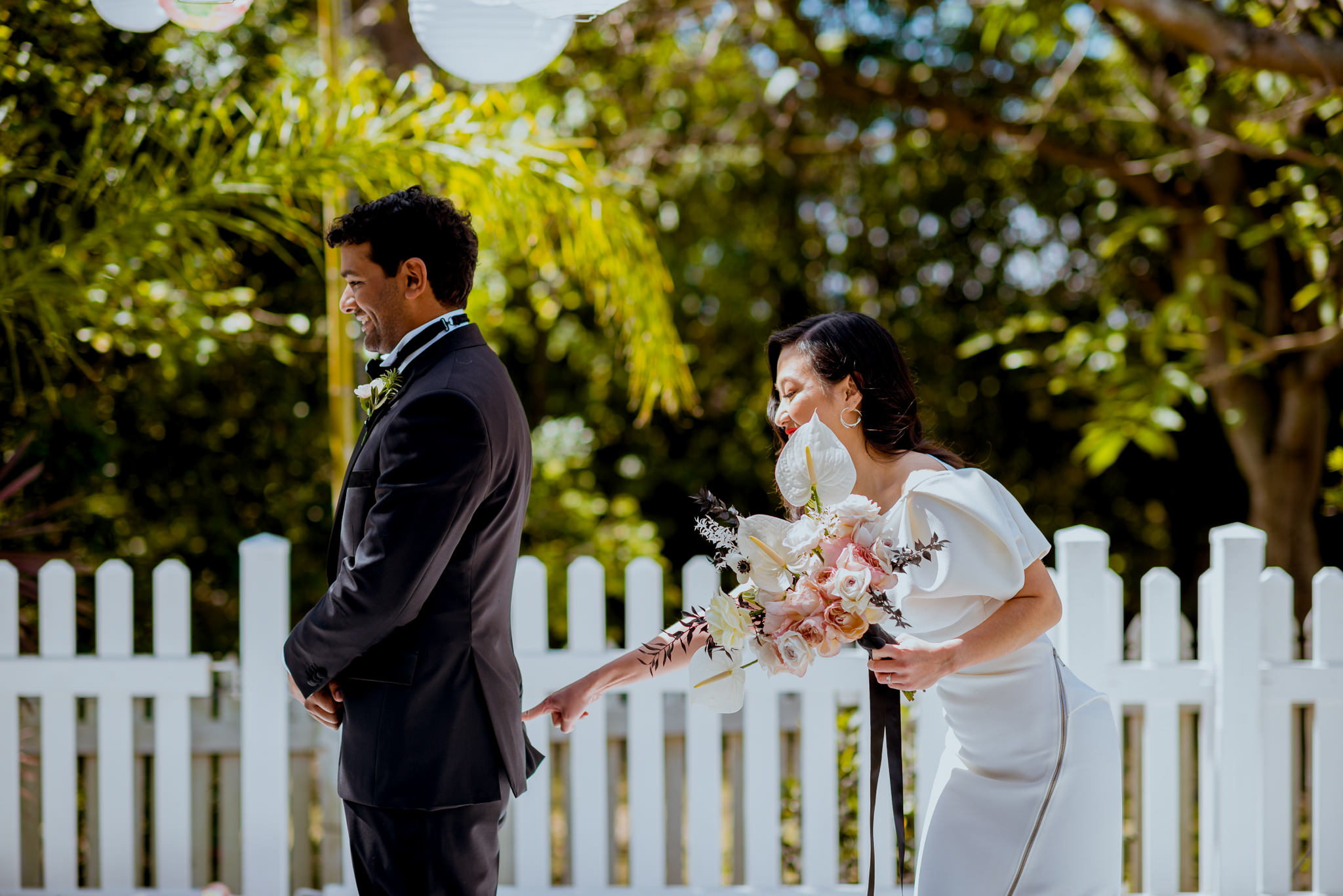 Bride playfully pokes groom's bum in front of a white picket fence