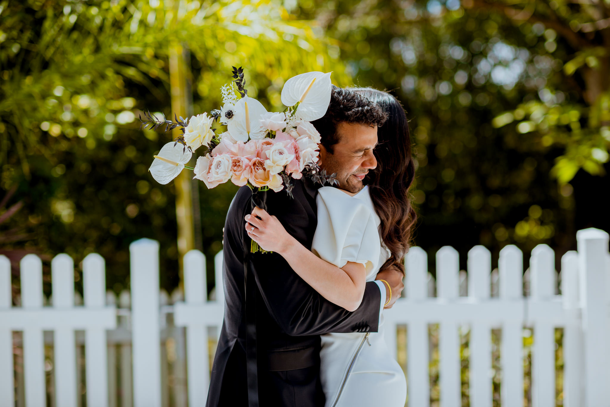 Groom in tears as he hugs his bride in front of a white picket fence