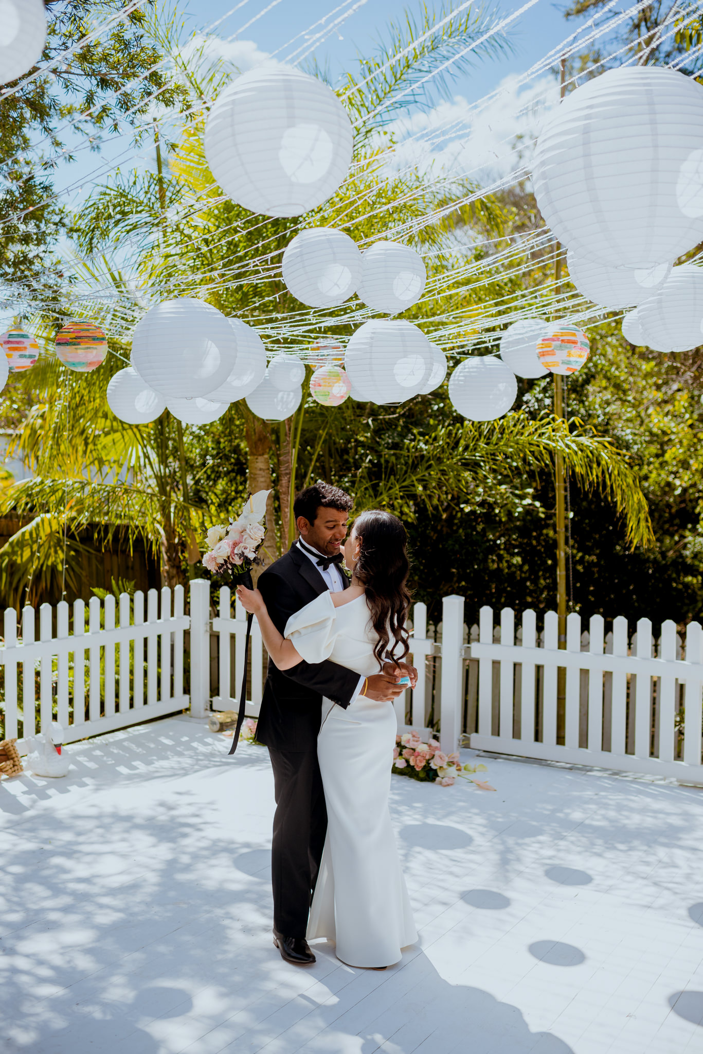 Groom and bride holding each other under white lanterns on a white wooden stage