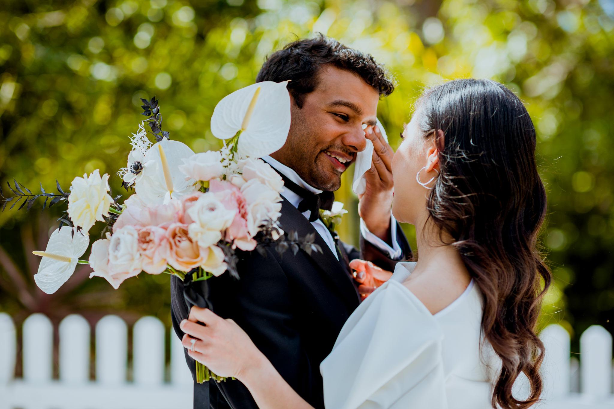 Groom wipes his tears as he talks to his bride