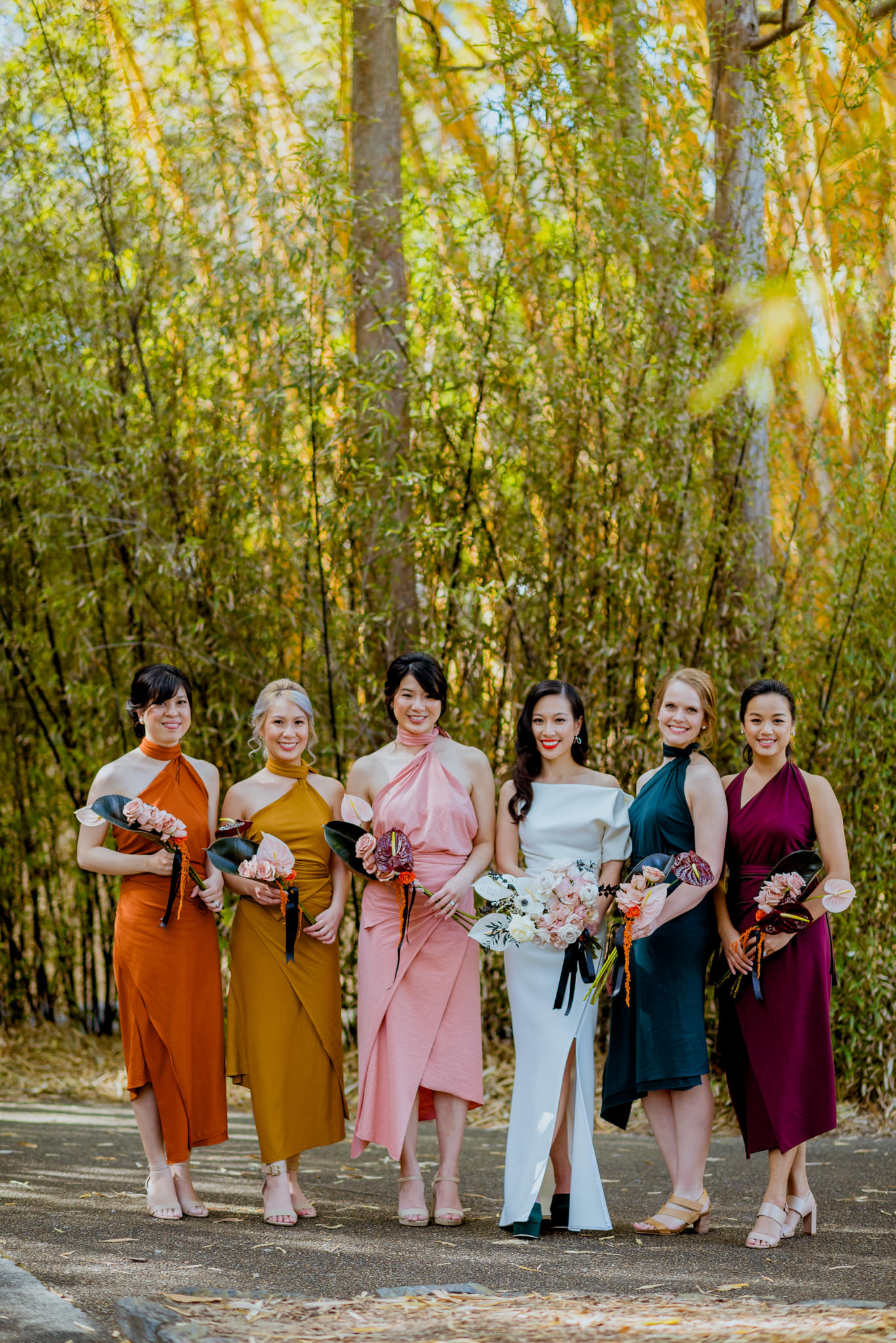 Bride and her bridesmaids standing, each in a different coloured dress