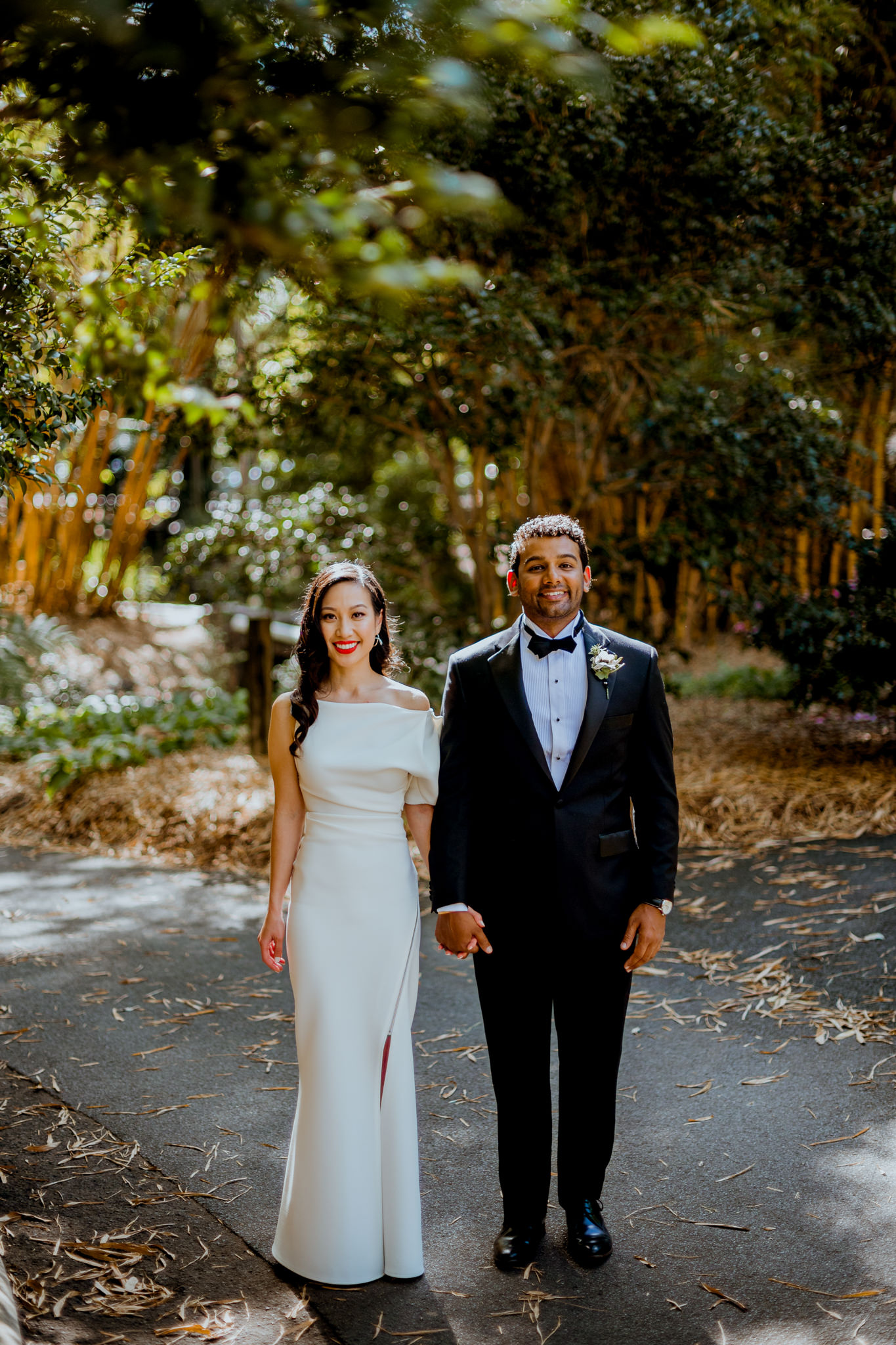 Asian bride and Indian groom standing towards camera in a bamboo garden