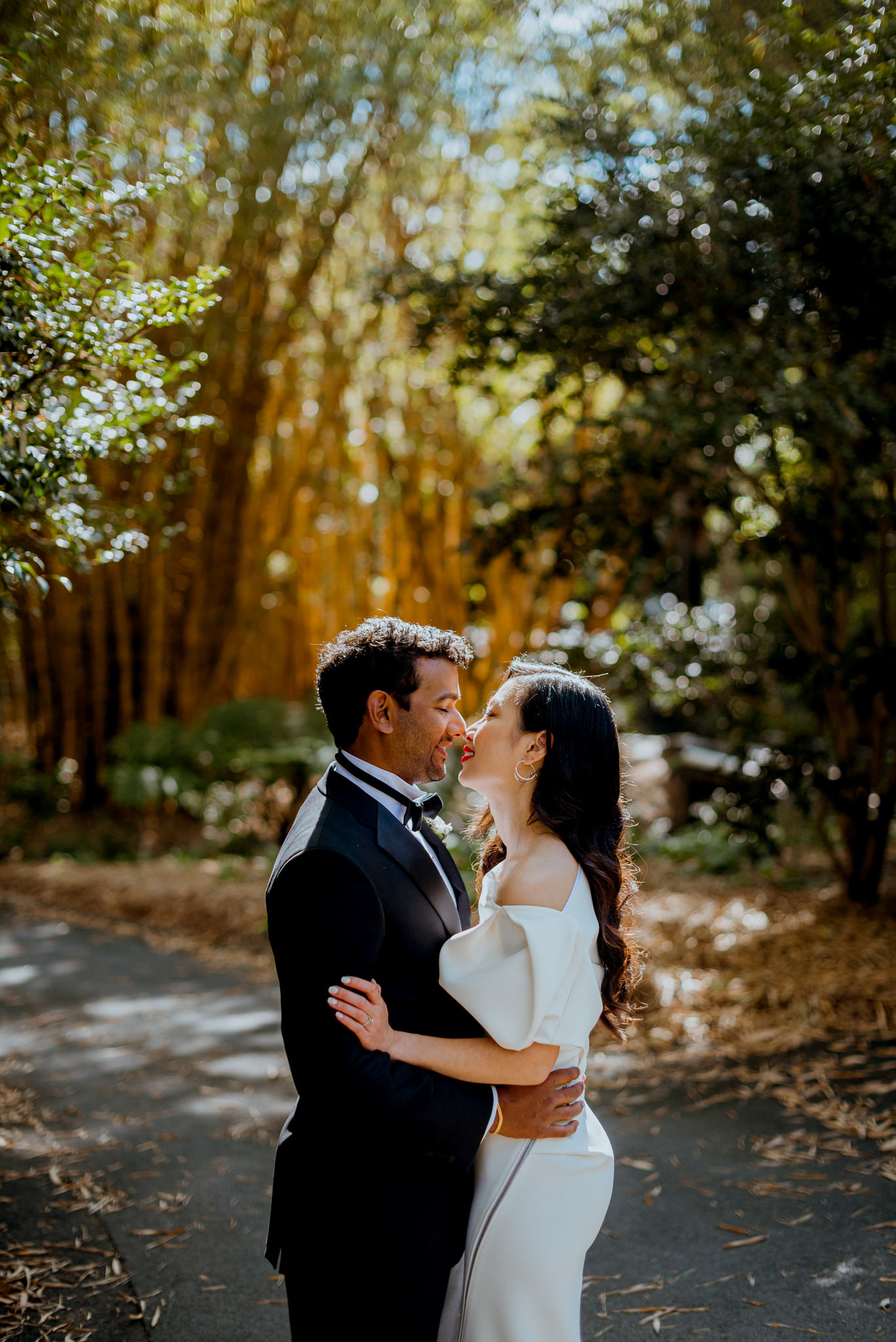 Asian bride and Indian groom almost kissing a in a bamboo garden