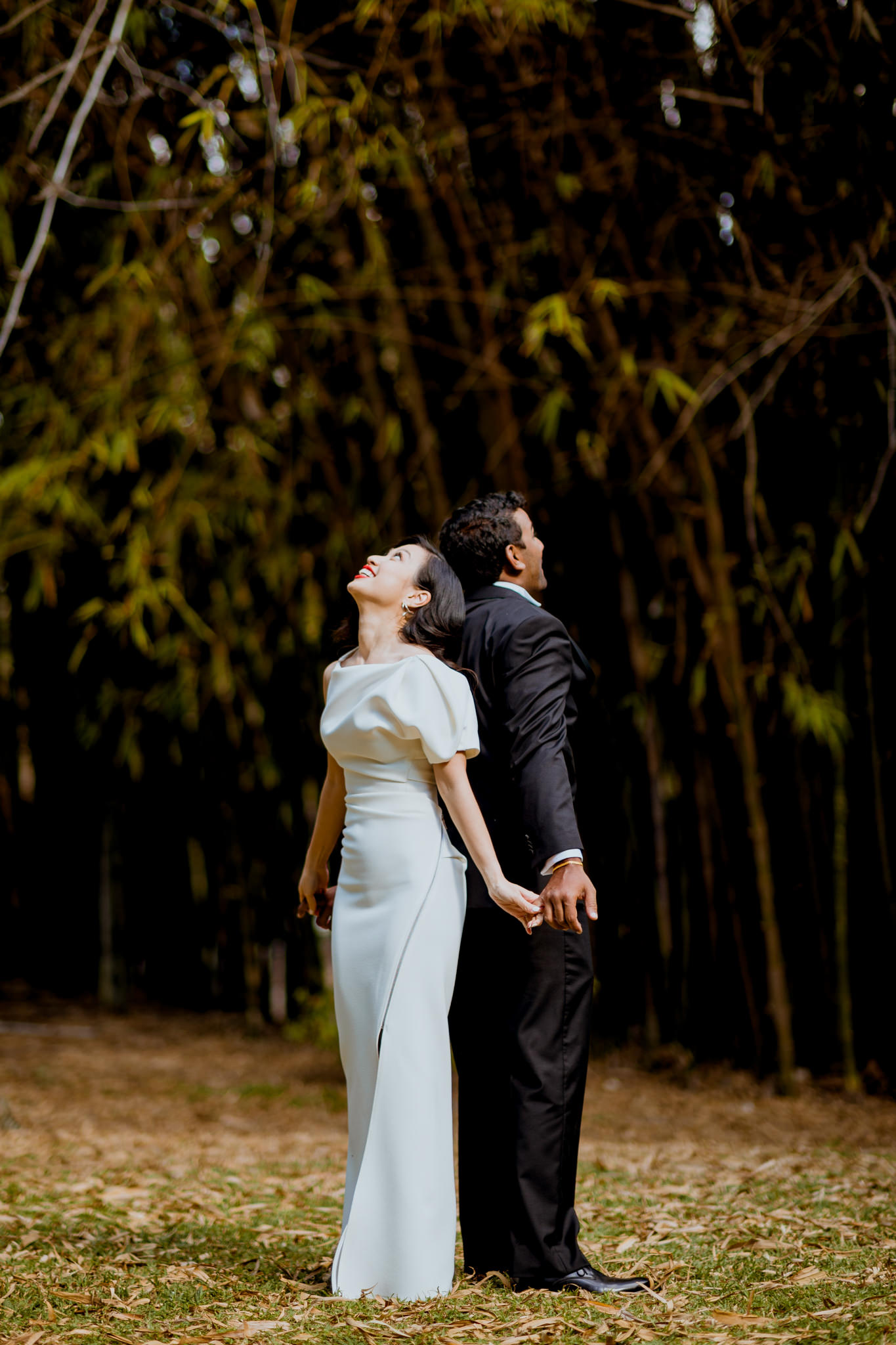 Bride and groom practicing first dance in front of bamboo trees