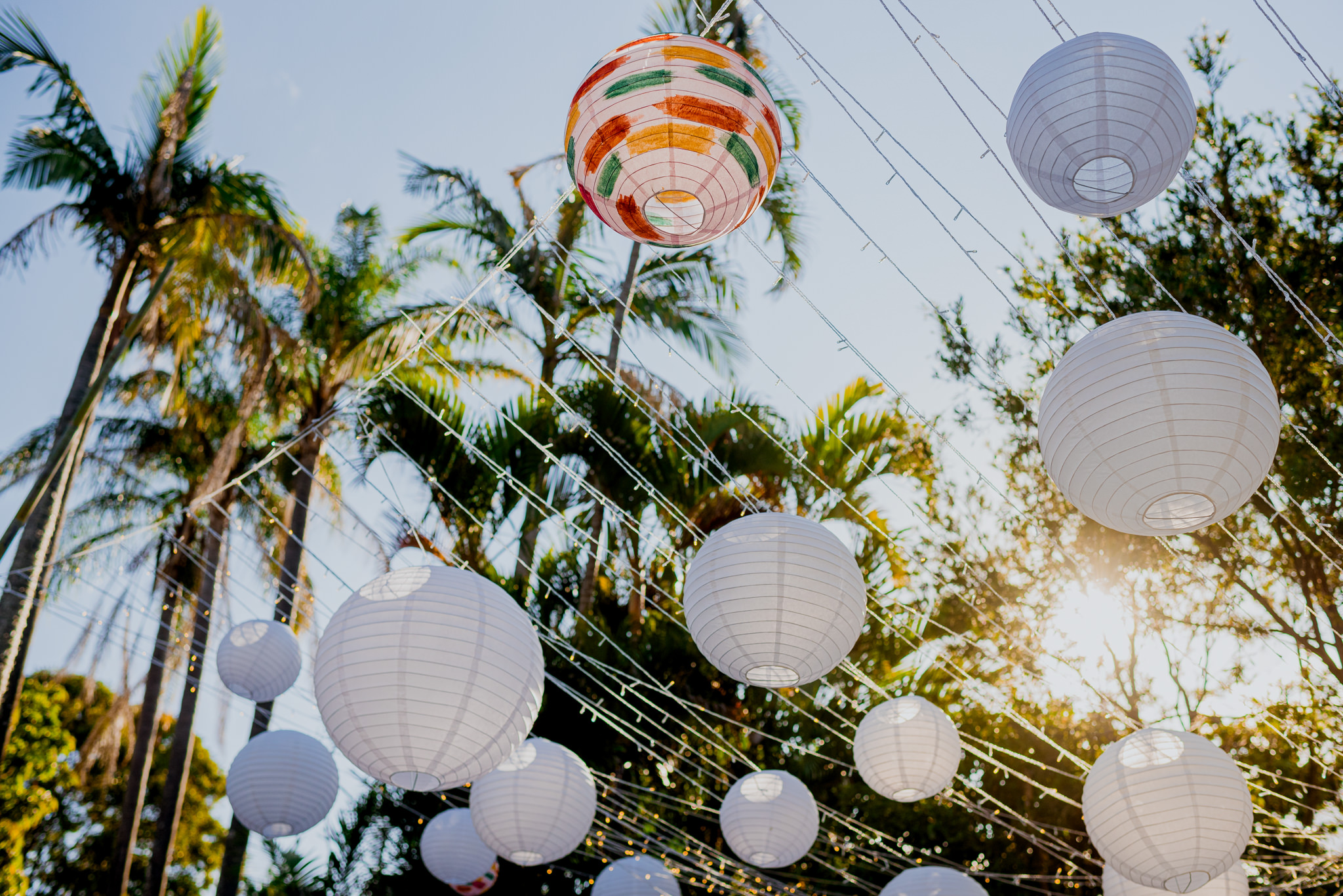 White lanterns strung up on lines of fairy lights, with one lantern painted colourfully and afternoon sun glowing behind them