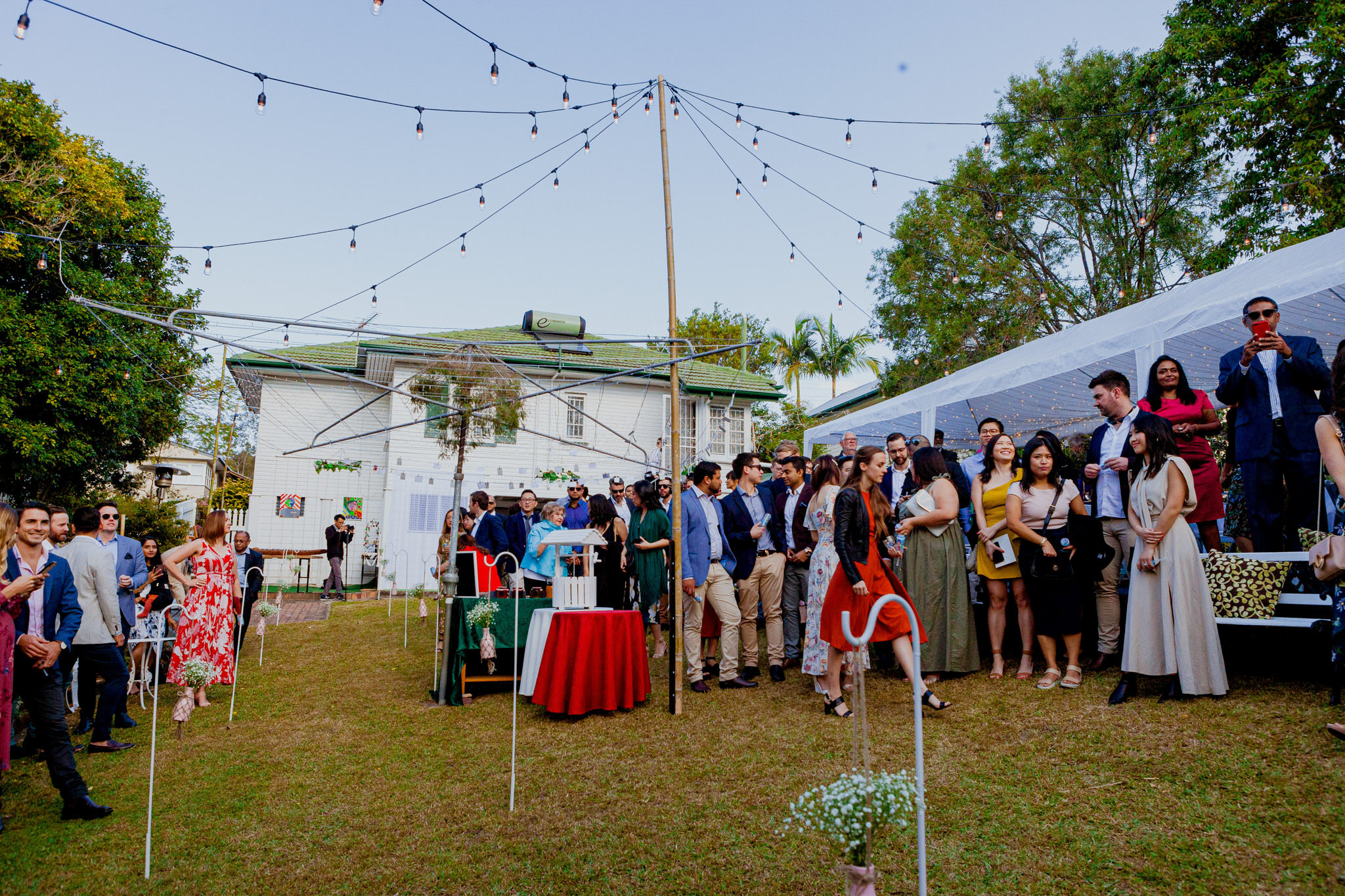 Dressed up crowd gathers in an Australian backyard before a wedding ceremony