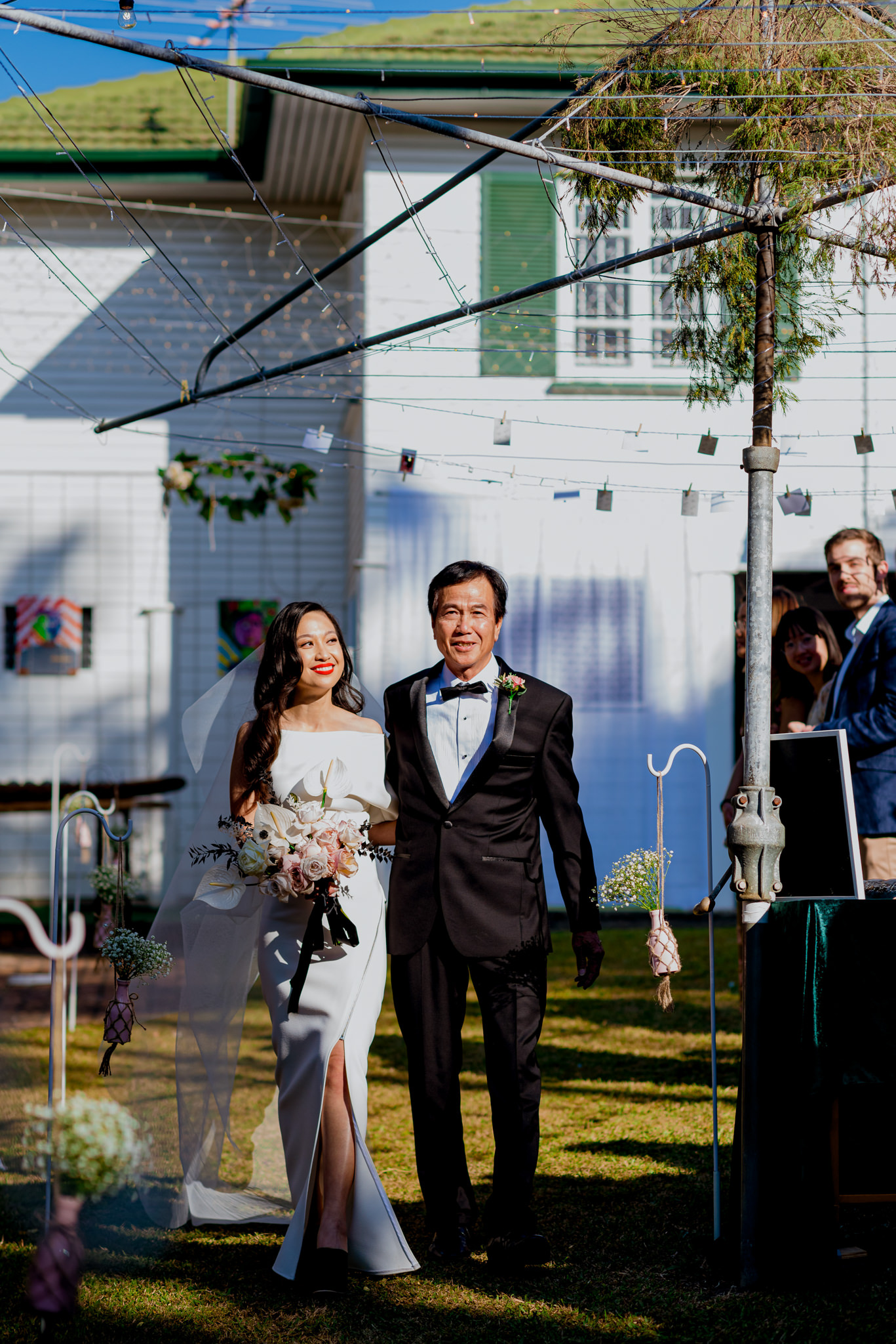 Asian father walks his daughter down the aisle in their backyard