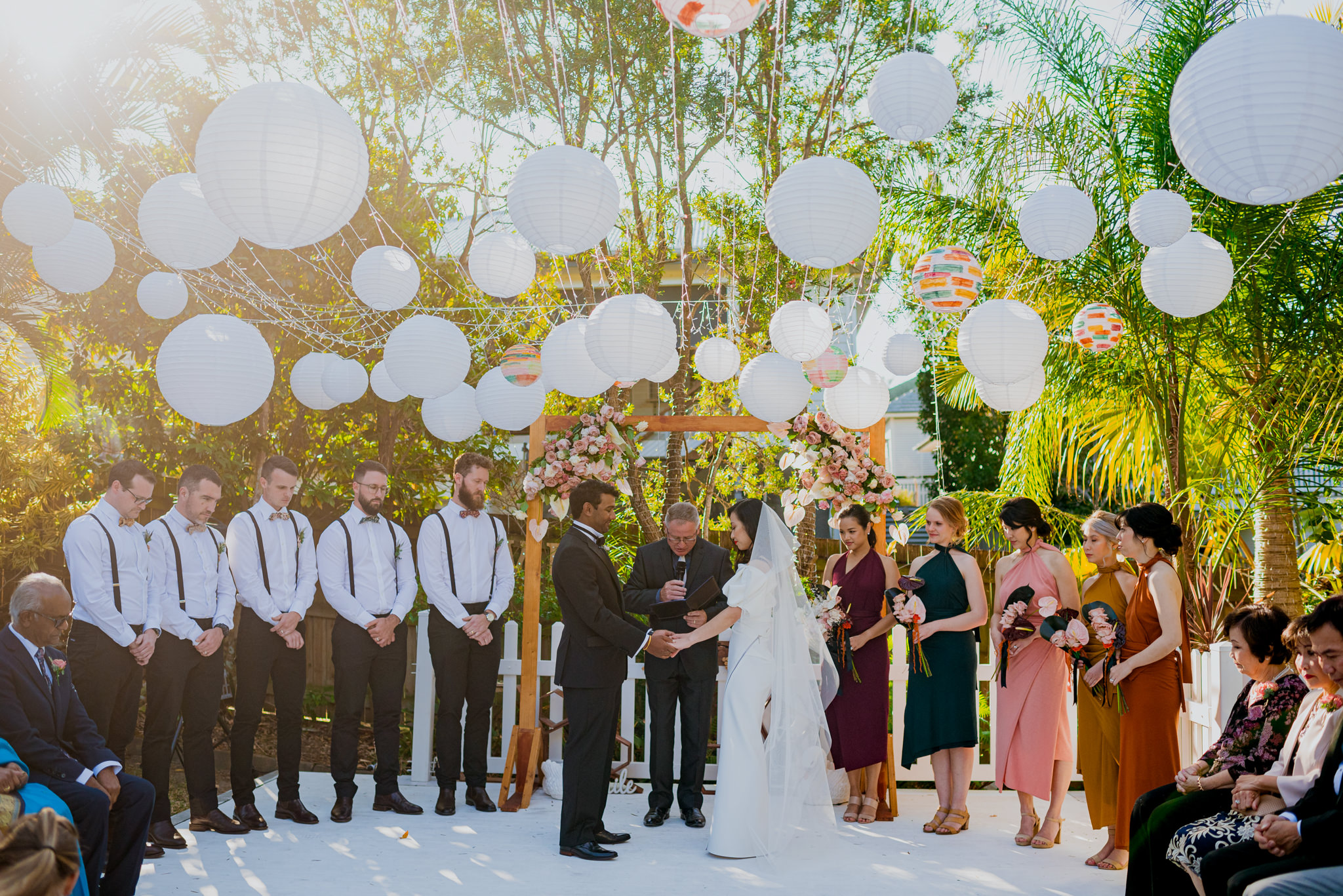 Bridal party praying together during a wedding ceremony in a garden