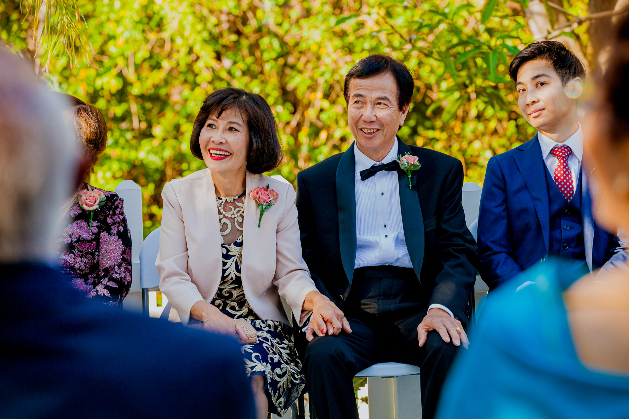Asian parents smile and laugh as they sit in formal attire