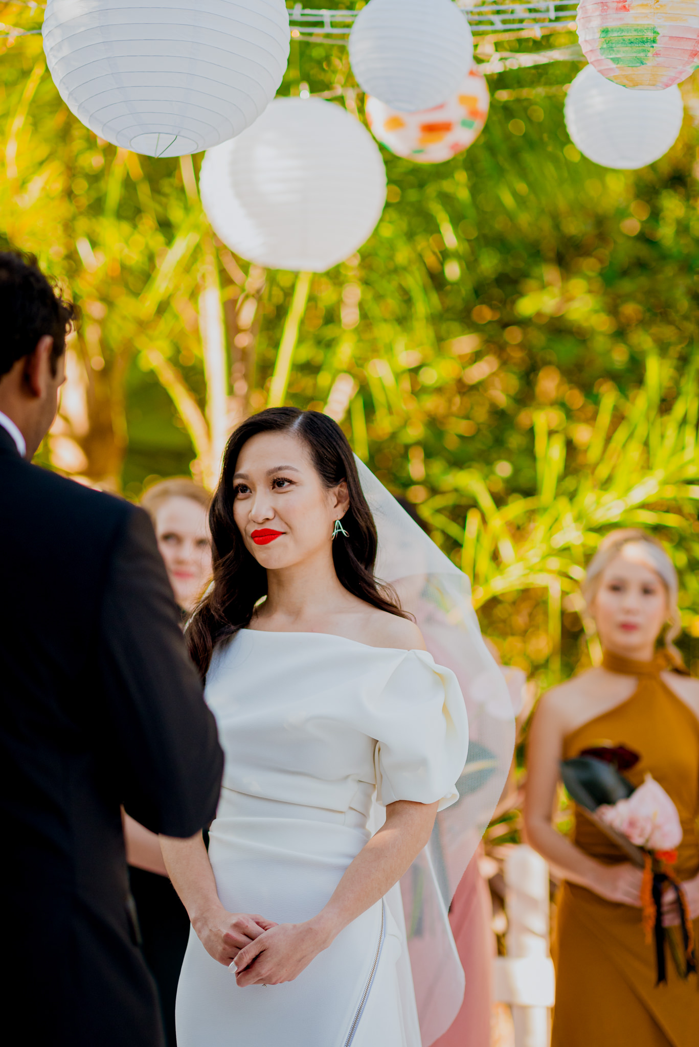 Asian bride listens to vows during wedding ceremony