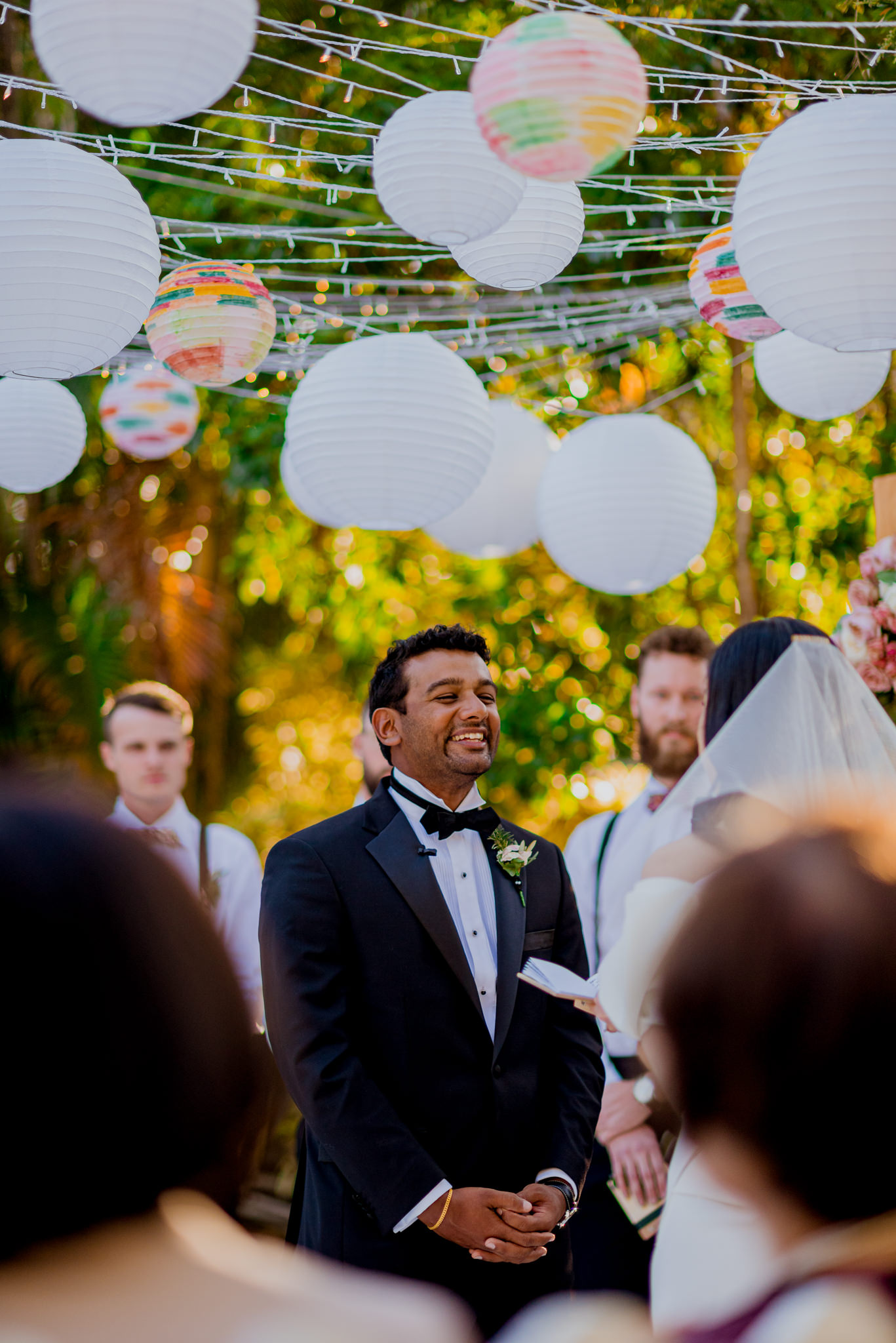 Asian groom laughs as he listens to vows during wedding ceremony