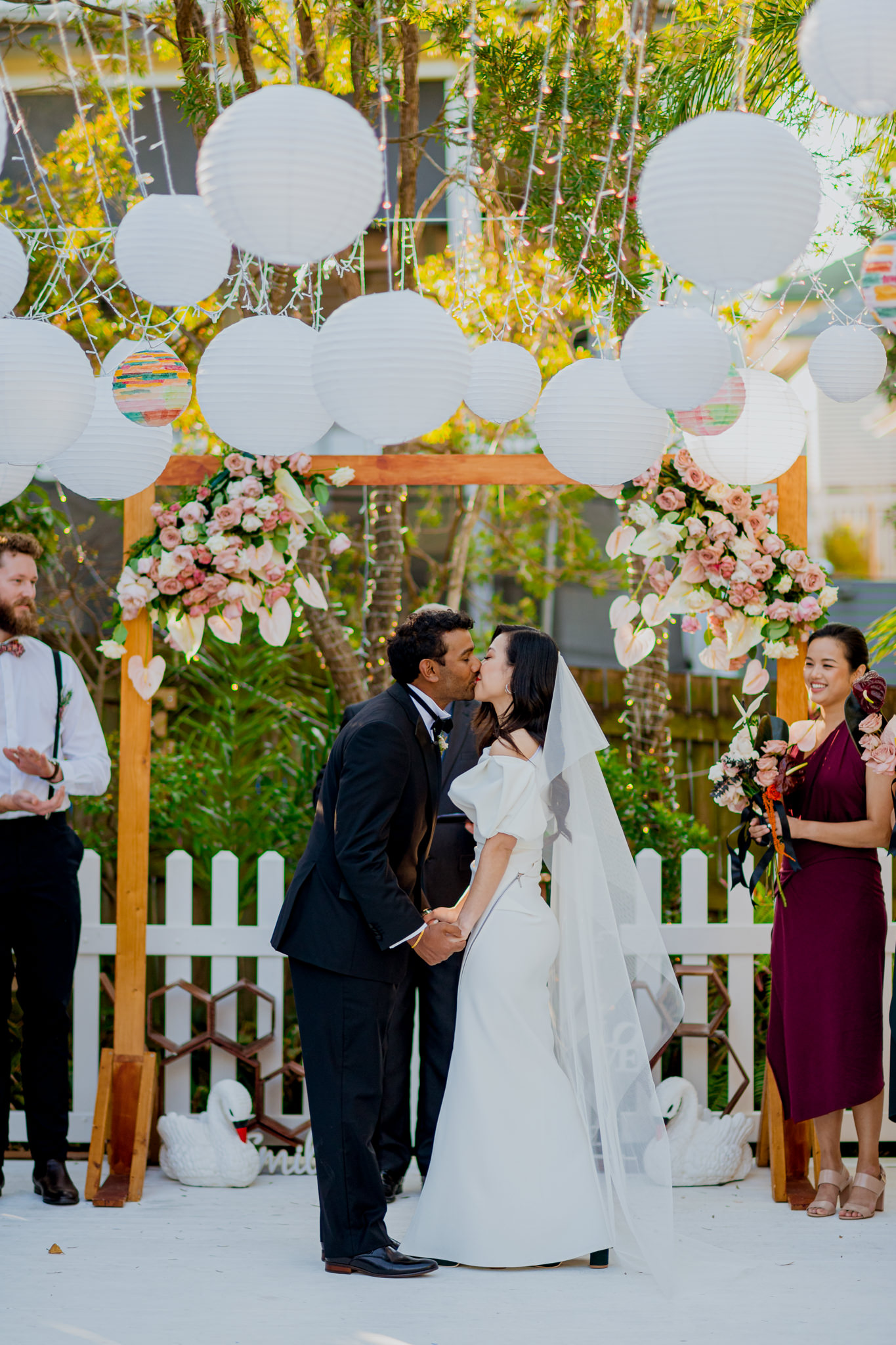 Wedding couple kisses during their wedding ceremony in a backyard