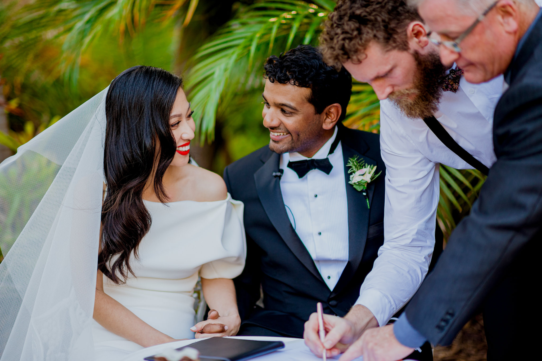 Bride and groom face each other and laugh as witness signs marriage certificate
